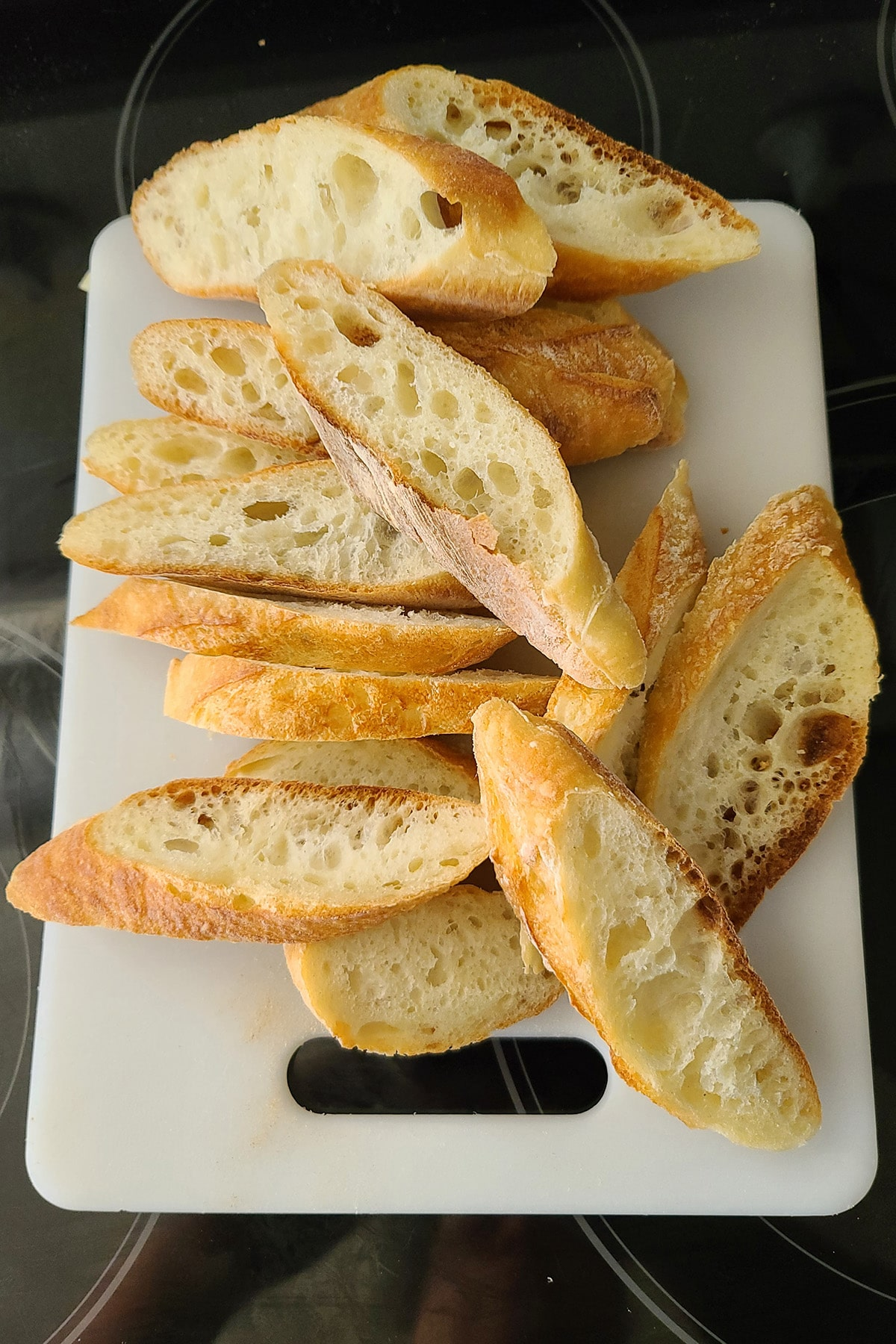 Slices of baguette in a pile on top of a white cutting board.
