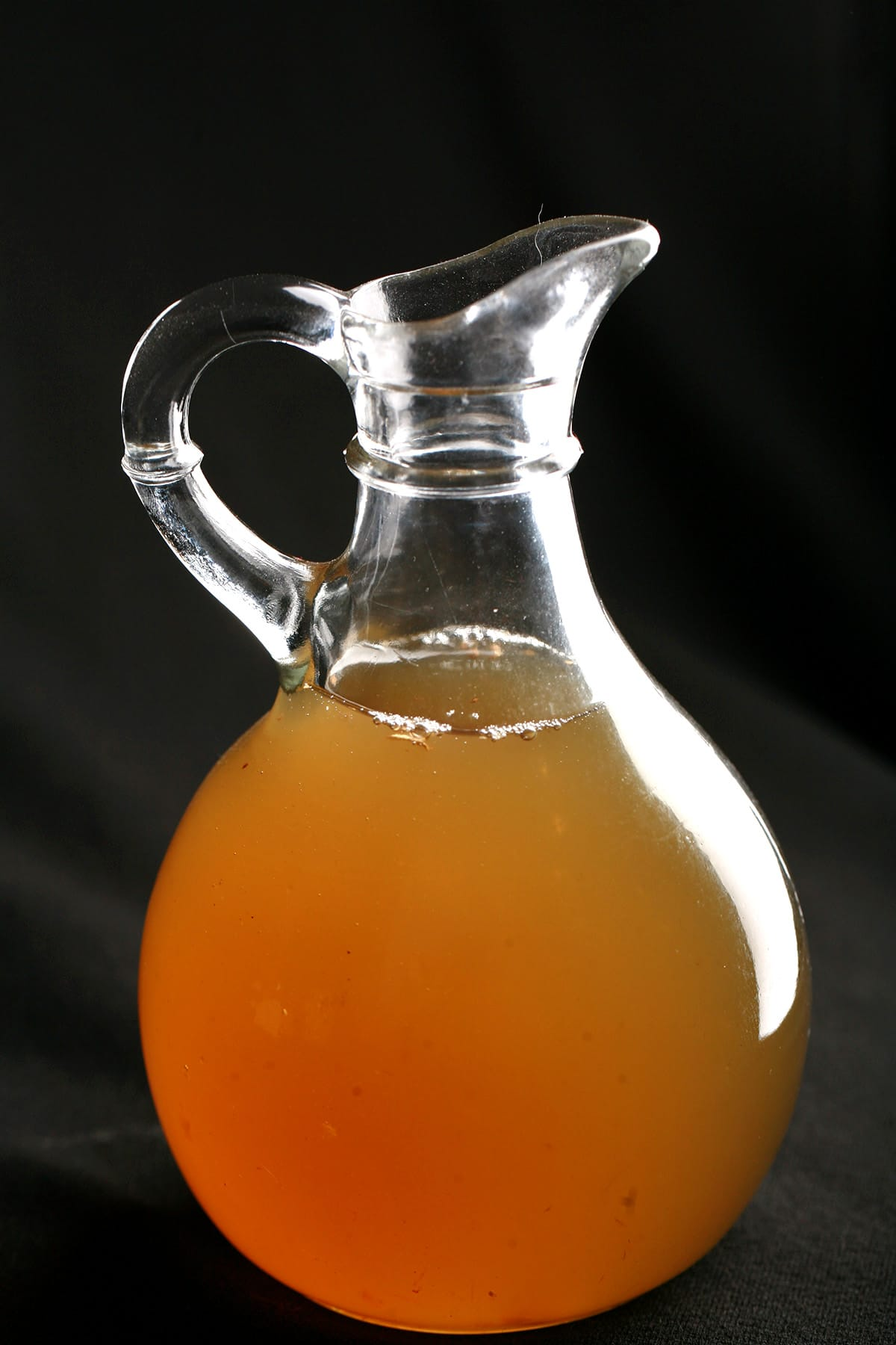 A small glass bottle of deep amber coloured ginger syrup.
