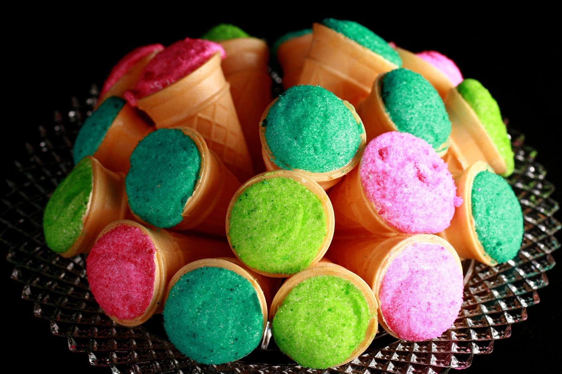 A pile of marshmallow cones - mini ice cream cones filled with marshmallow - are arranged on a plate. The exposed marshmallow of each is coated in colourful sugar - hot pink, lime green, and teal.