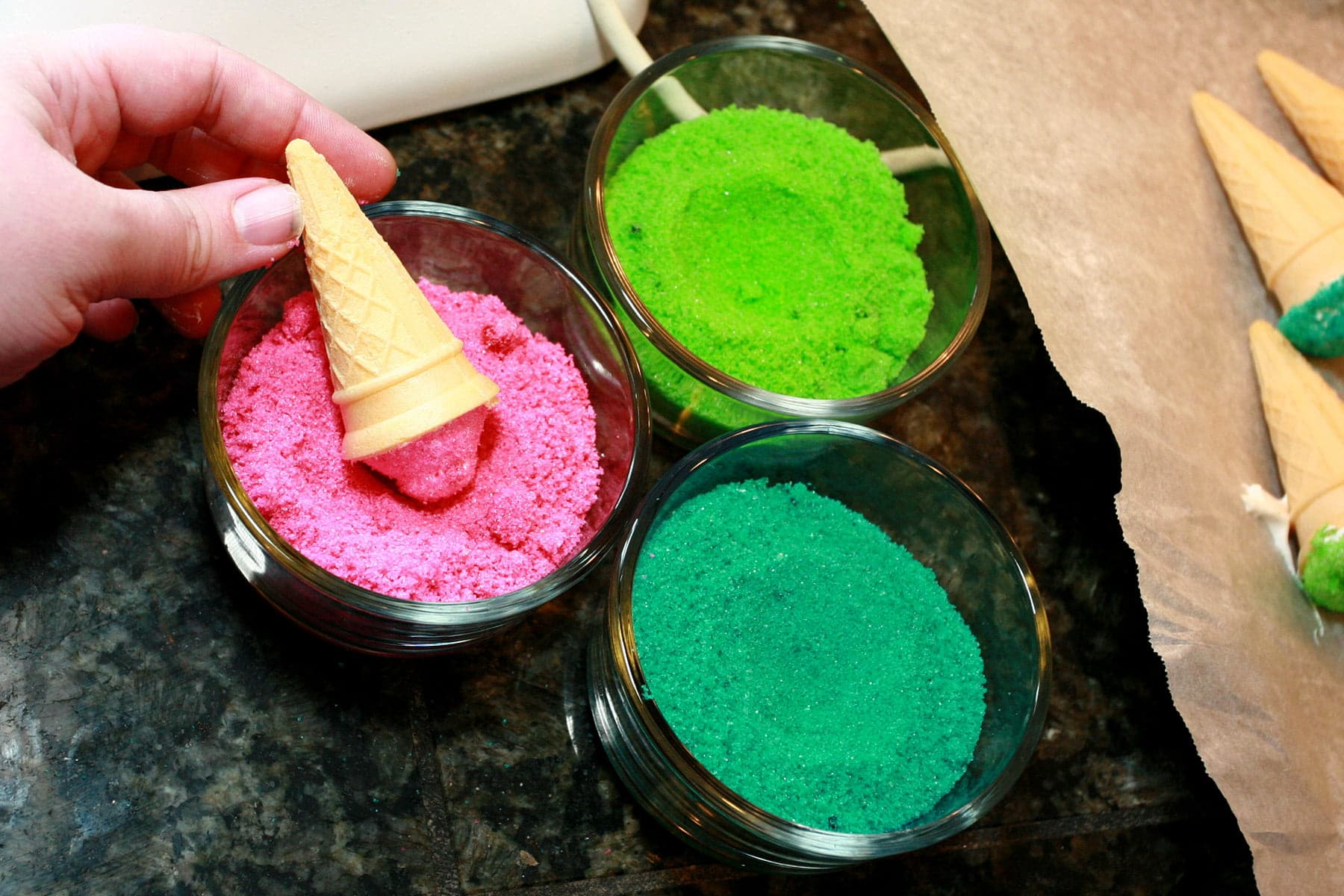 3 bowls of colourful sugar - hot pink, lime green, and teal. A hand twirls a freshly piped marshmallow cone in the pink sugar.