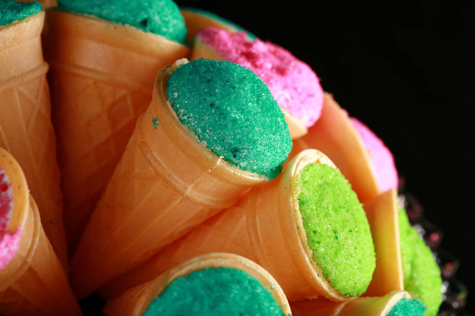 A pile of mini ice cream cones are arranged on a plate. The exposed marshmallow of each is coated in colourful sugar - hot pink, lime green, and teal.