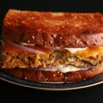 A close up photo of a toasted sandwich with polenta, mushrooms, wild rice, cheddar, red onions, and mayo visible.
