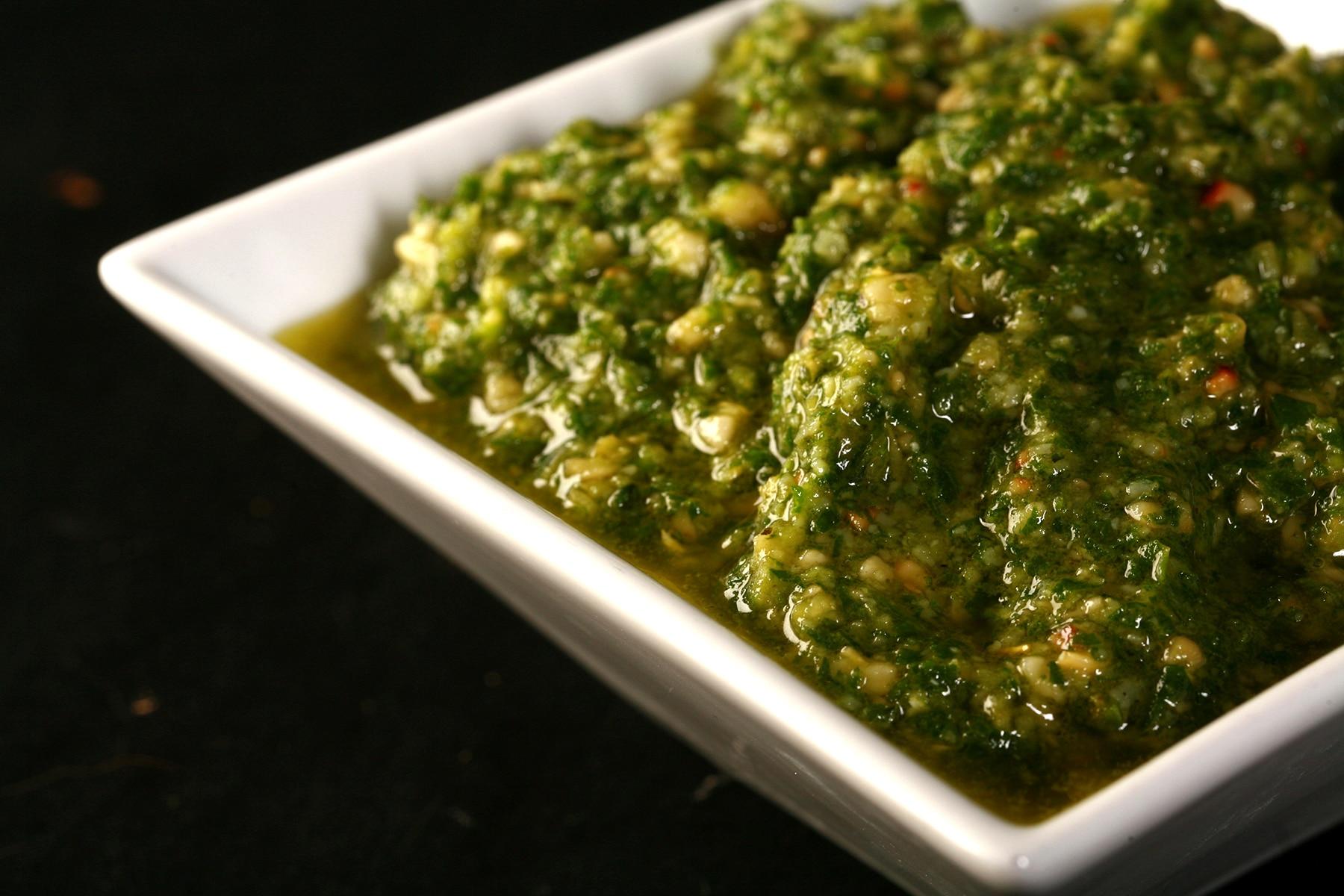 A small white bowl full of homemade basil pesto.