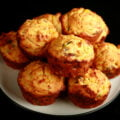 A white plate stacked with a pile of breakfast corn muffins. Bits of cheese and green onion are visible in the muffins.