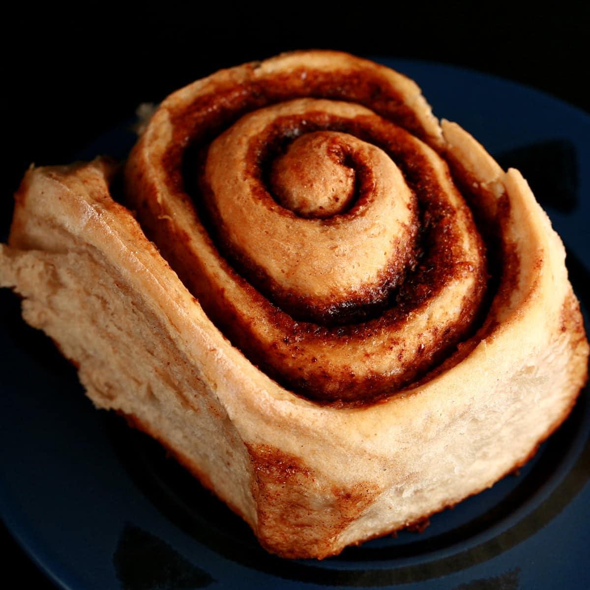 A single chai cinnamon bun on a plate.