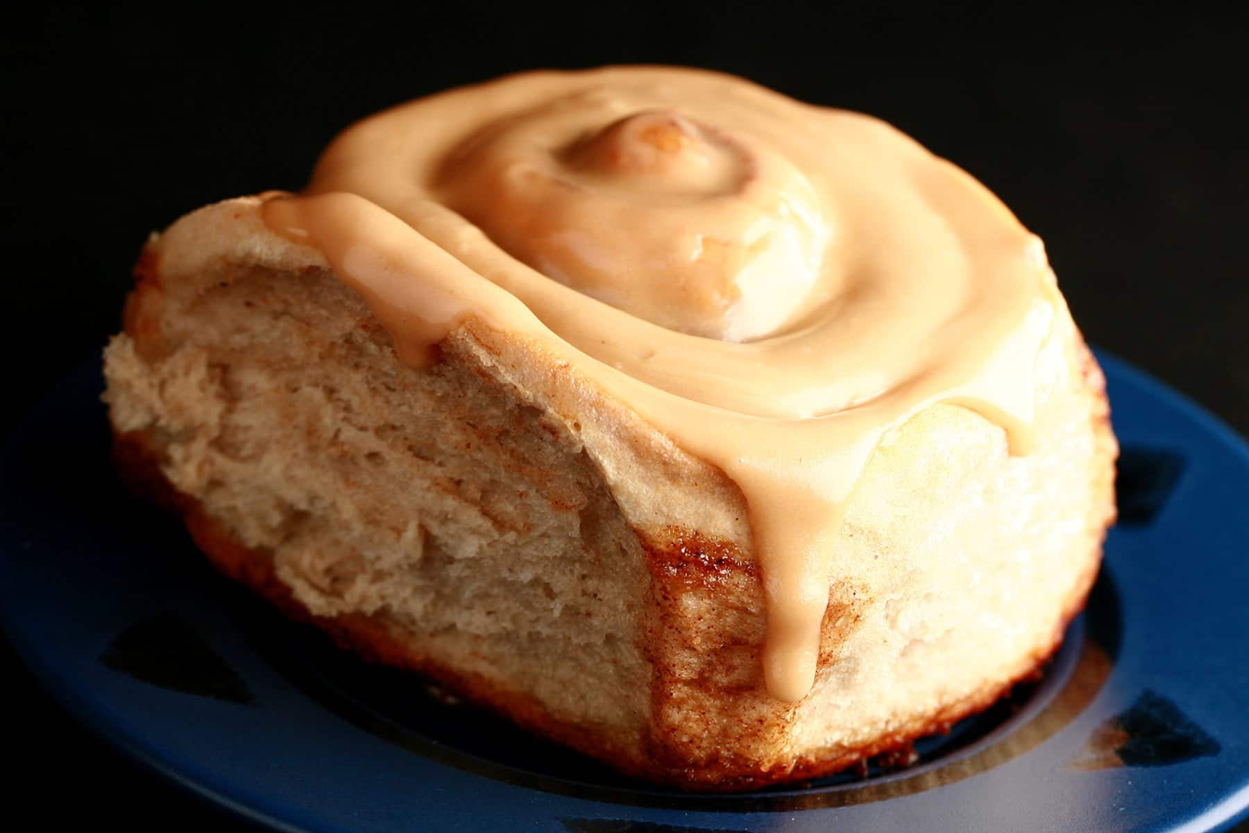 A close up view of a chai cinnamon roll, glazed with a light tan, tea flavoured frosting.