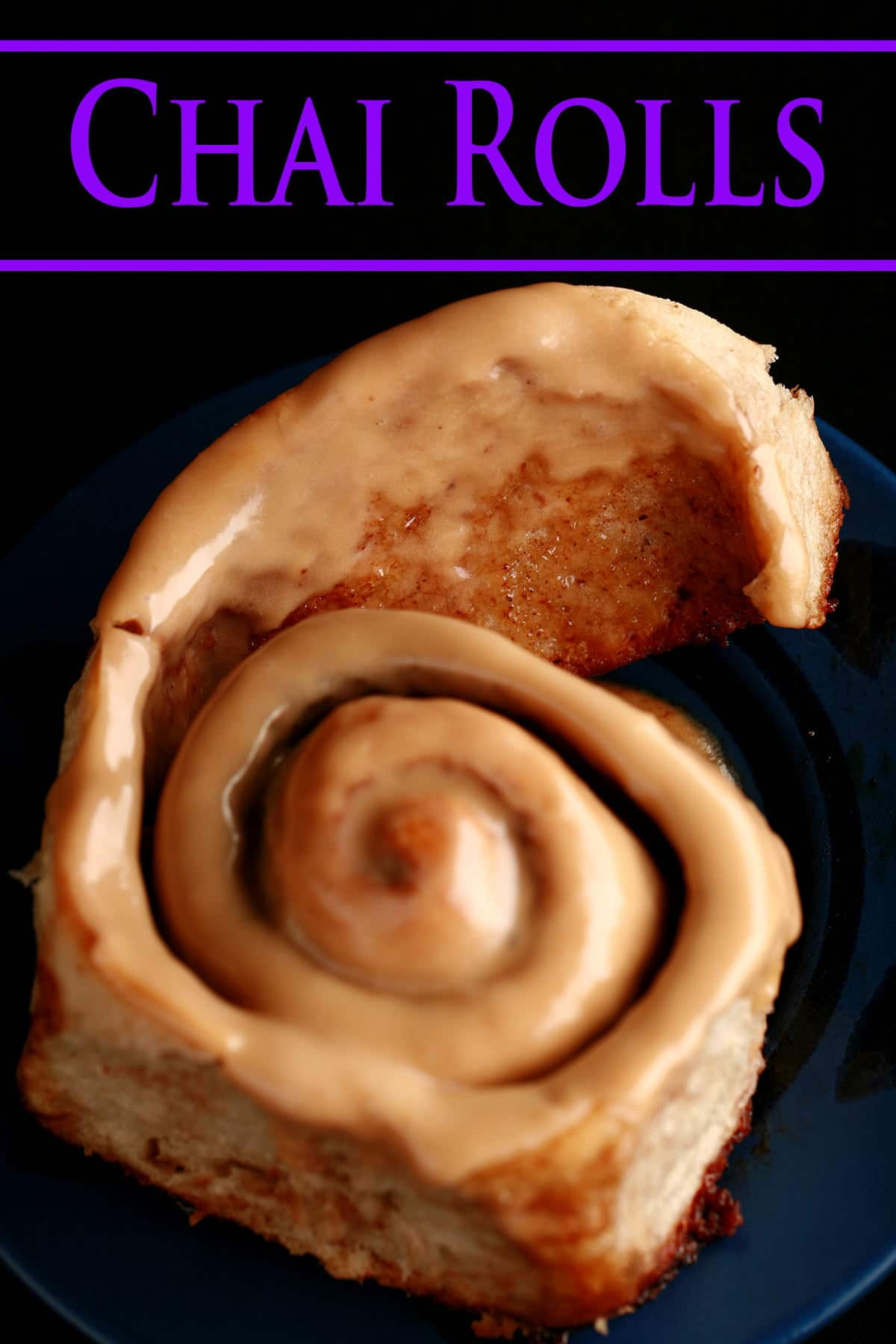 A close up view of a chai cinnamon bun, glazed with a light tan, tea flavoured frosting.