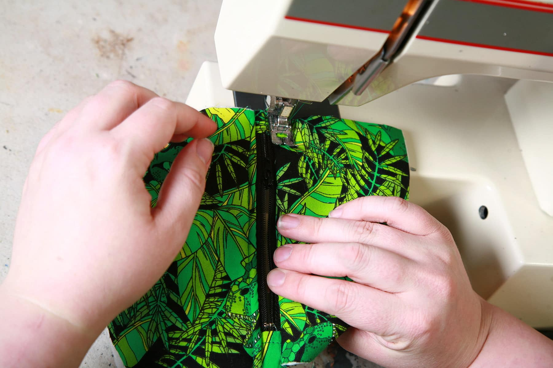 Two hands are shown using a sewing machine to sew a black zipper onto a green printed fabric.