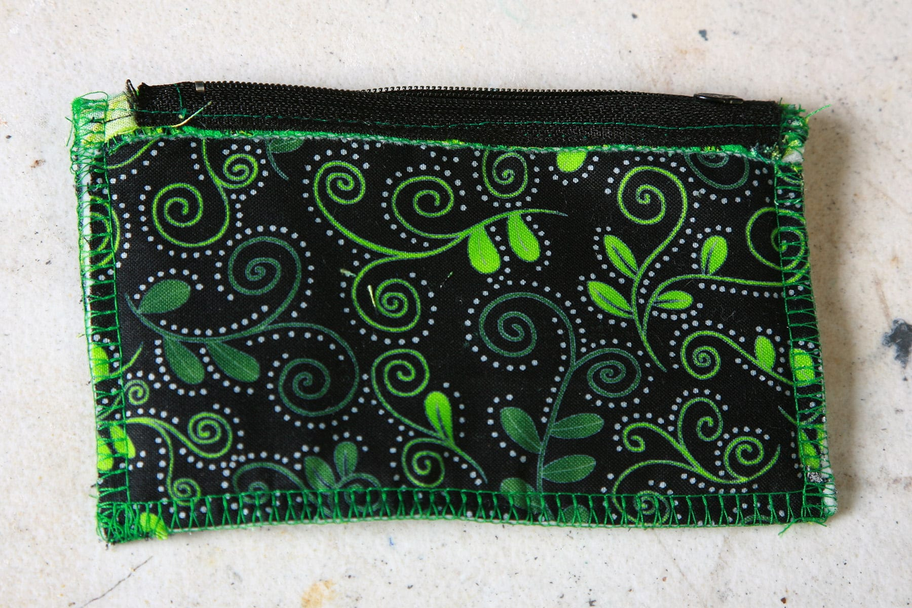 The finished coin purse is shown inside out, The lining fabric - black with thin green swirls - is what's showing.