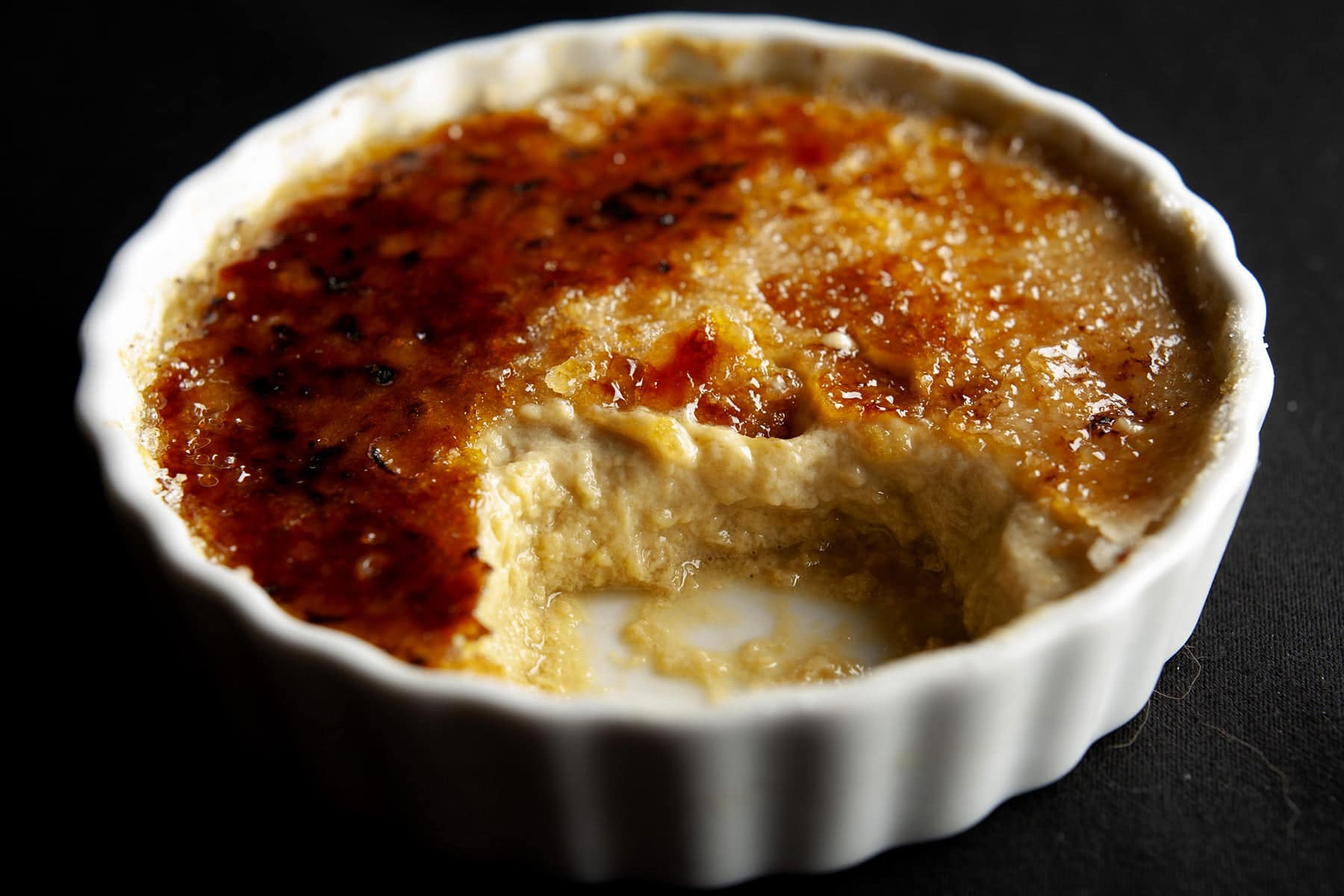 A close up view of a small white ramekin with creme brulee in it. The top is coated with crunchy, golden brown melted sugar, and part of the dessert is missing, having been spooned out and eaten.