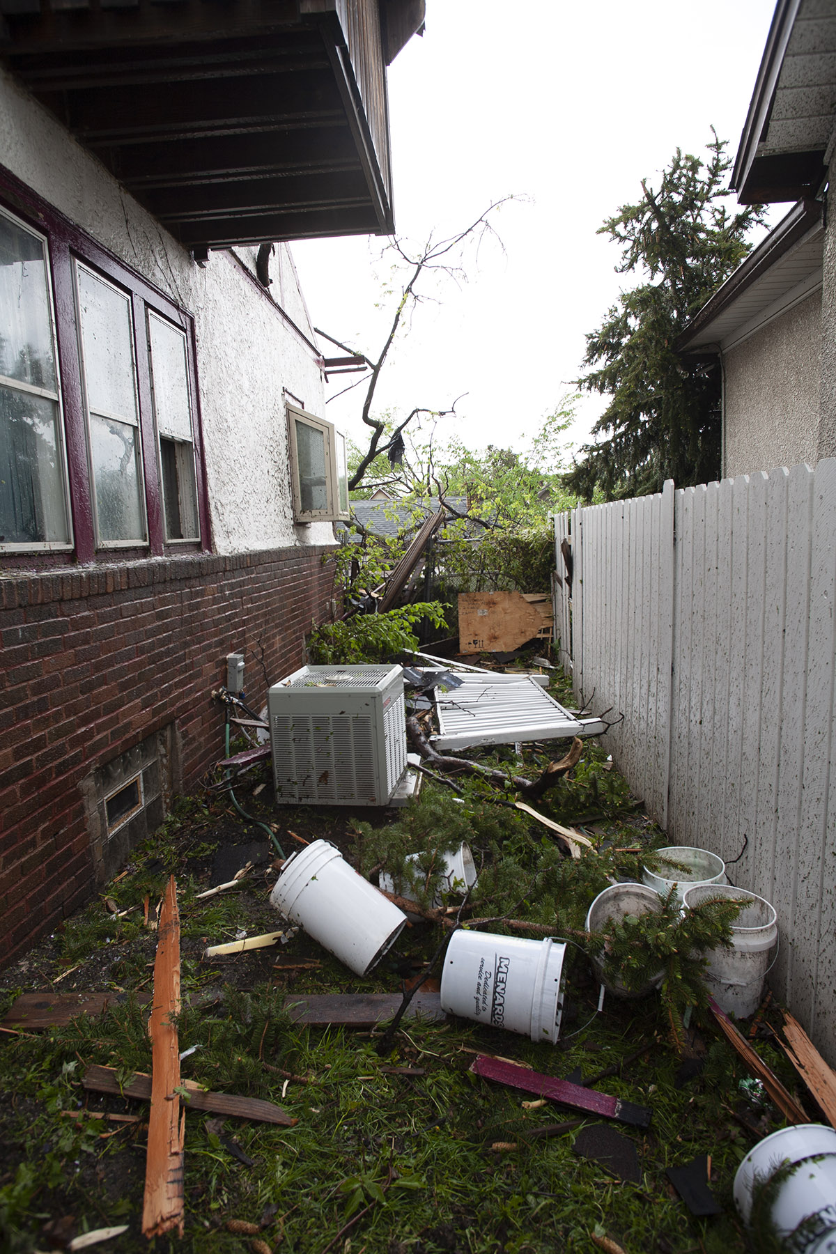 Photo of the side yard of a tornado smashed house. Debris everywhere.