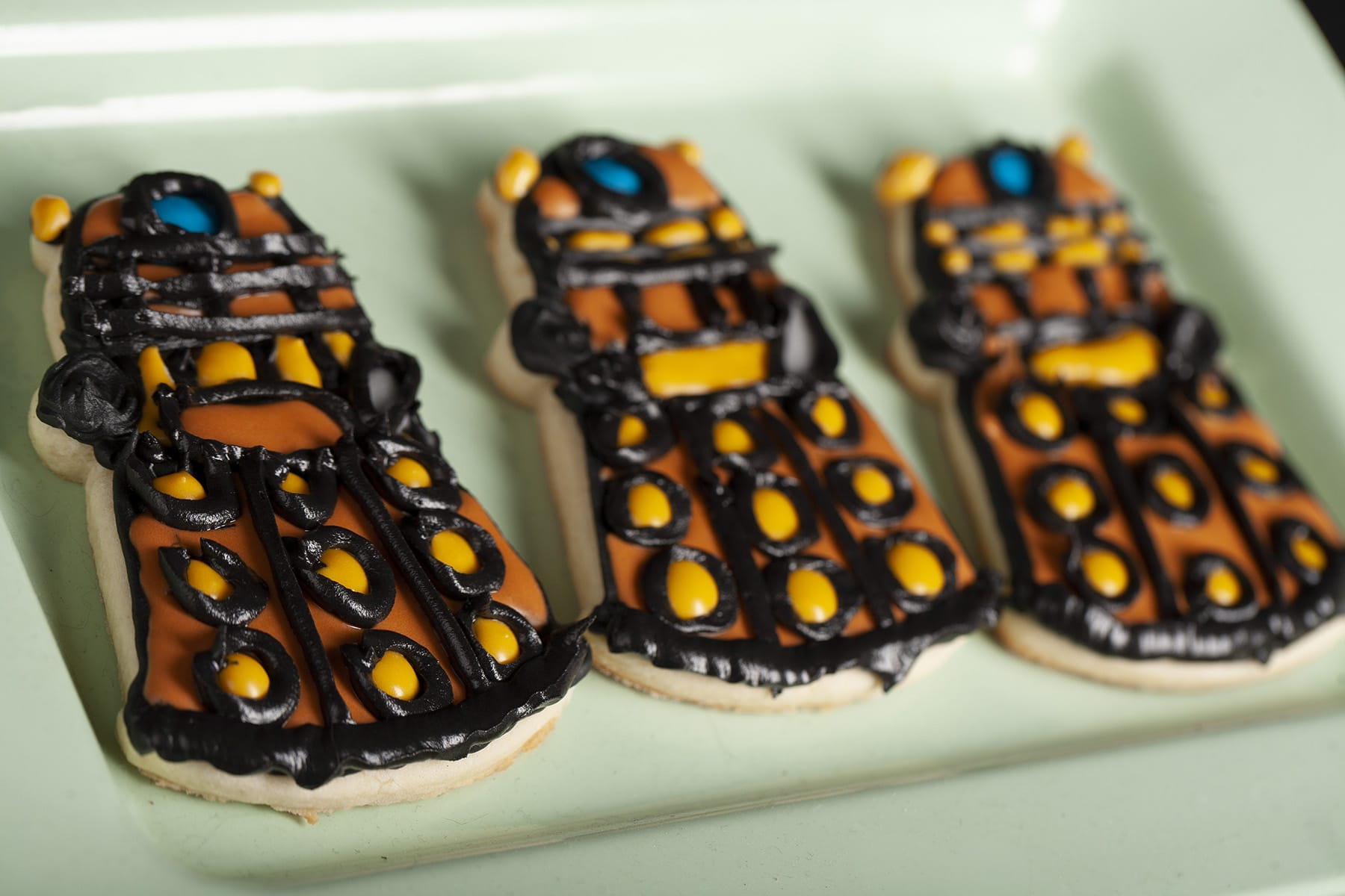3 decorated Dalek sugar cookies on a light green plate.