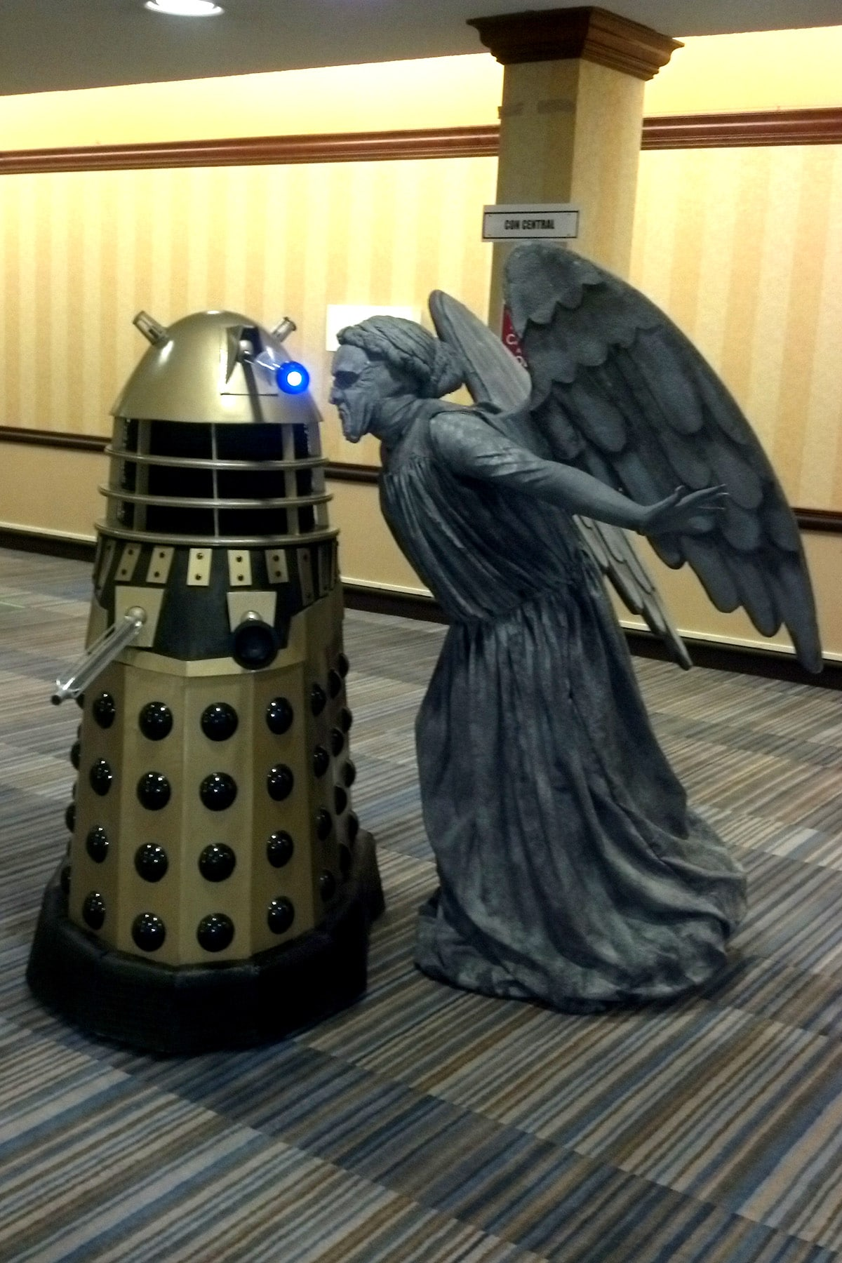 A cosplayer dressed as a Weeping Angel, leaning in to kiss a Dalek.