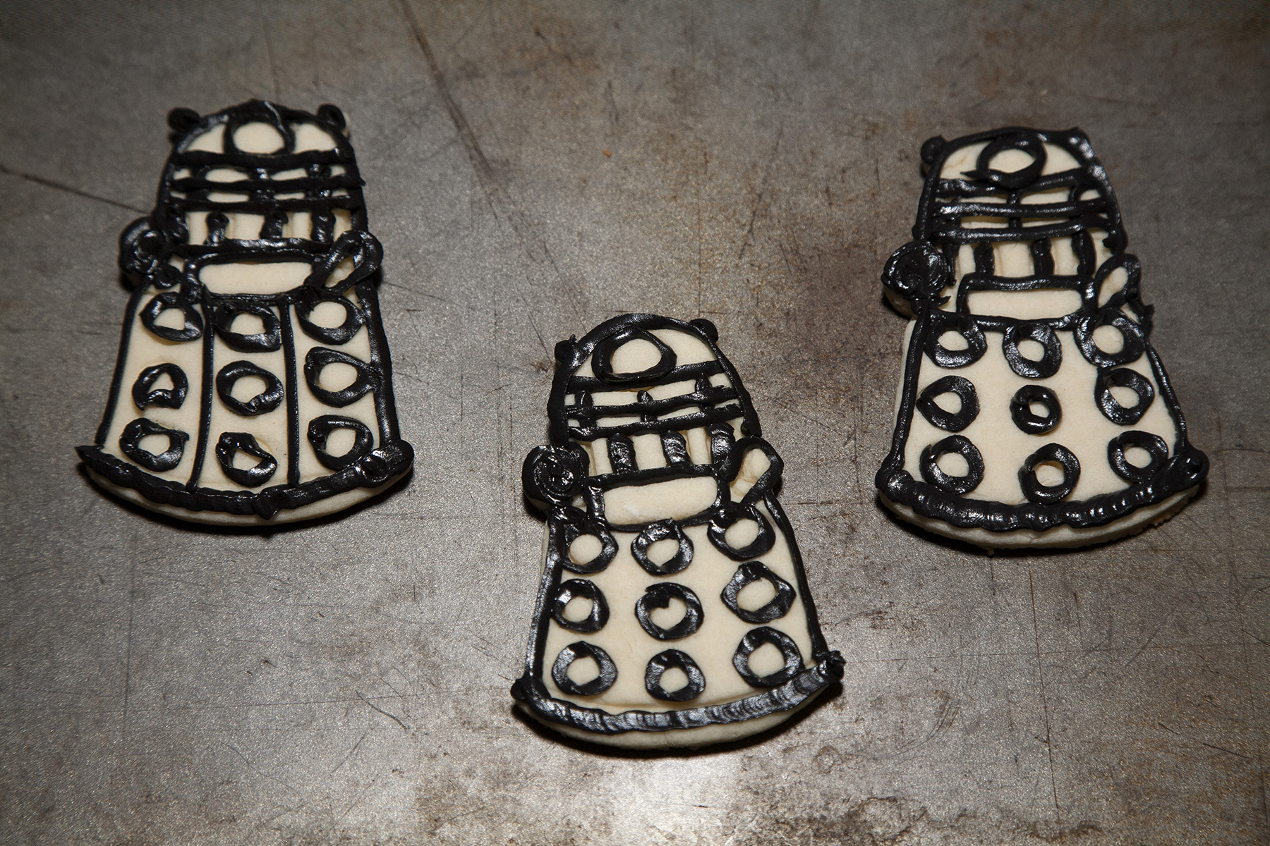 2 Dalek sugar cookies, completely outlined with black frosting.