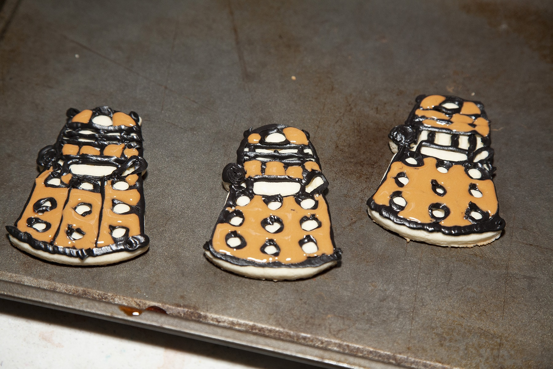 3 Dalek cookies with the main areas filled in with brown frosting.