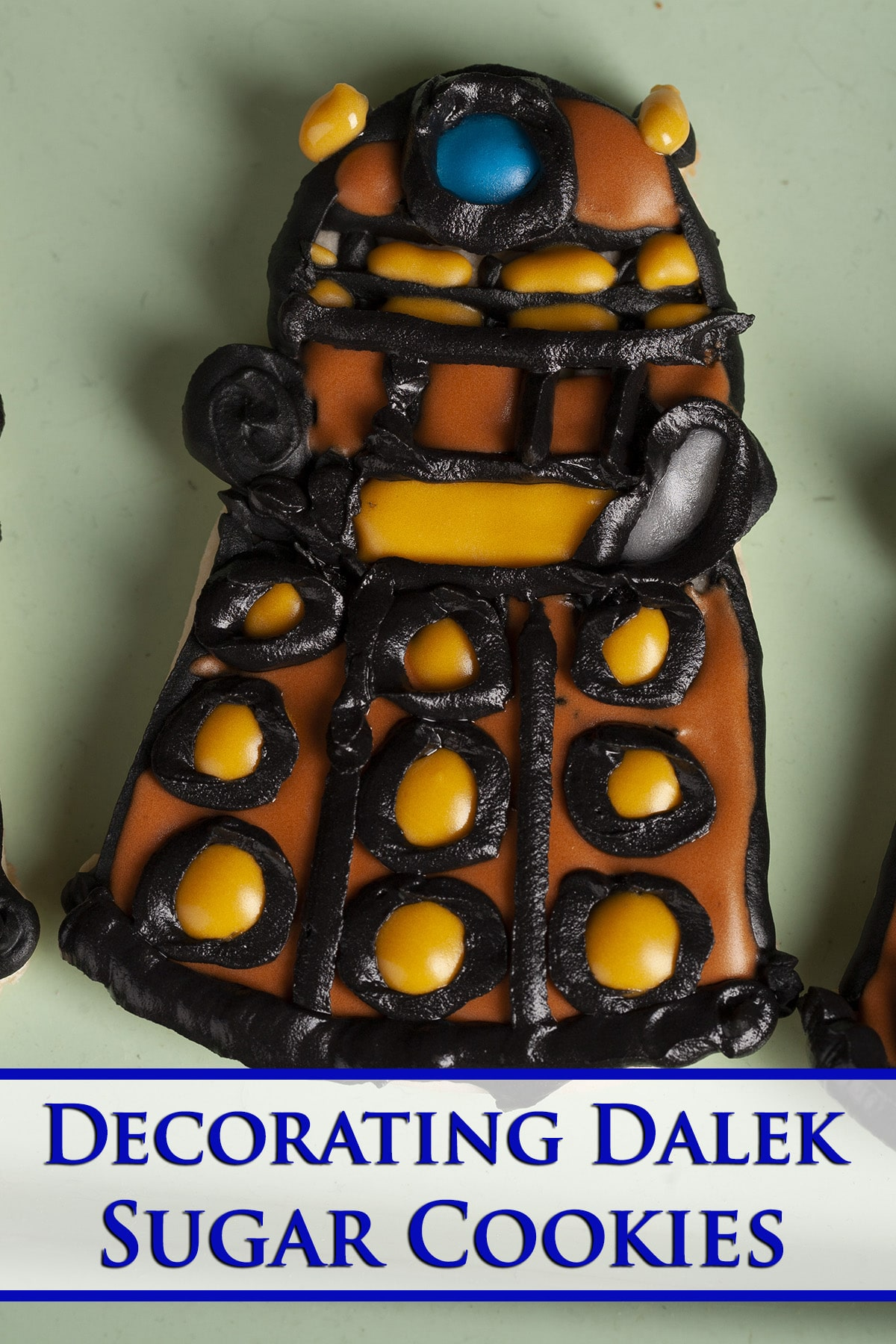 """A decorated sugar cookie. Blue text overlay says """"Decorating Dalek Sugar Cookies""""."""