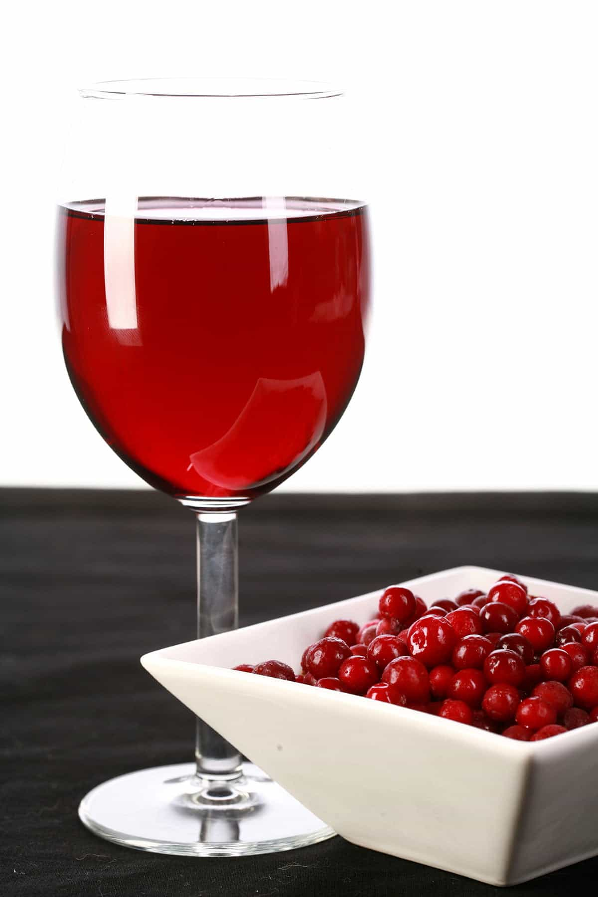 A glass of red wine - made from this lingonberry wine recipe - is pictured next to a small bowl of lingonberries.