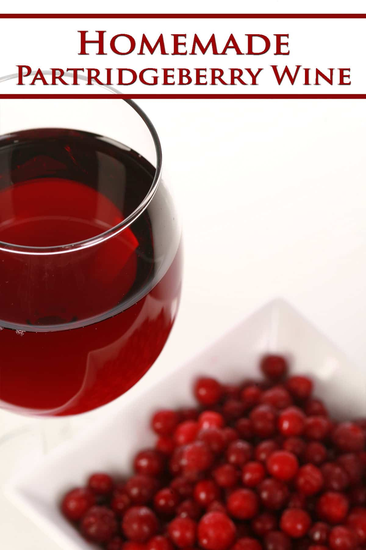 A glass of red wine - made from this partridgeberry wine recipe - is pictured next to a small bowl of partridgeberries.
