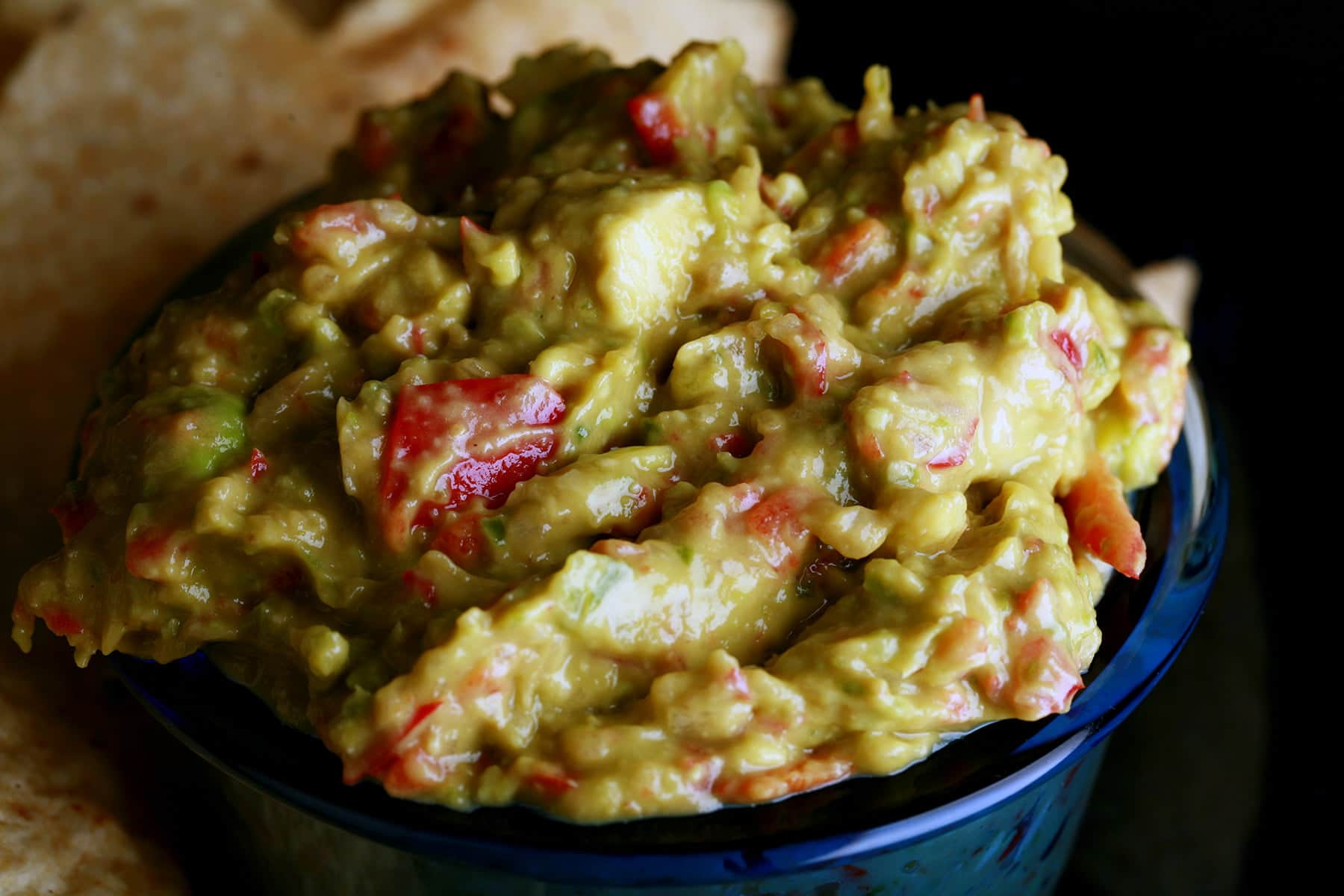 A plate of corn chips is shown with a bowl of chunky guacamole.