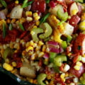 A close up photo of roasted corn and potato salad. Chunks of red potato, bacon pieces, celery slices, green onion, and corn kernels are all visible in the colourful mix.
