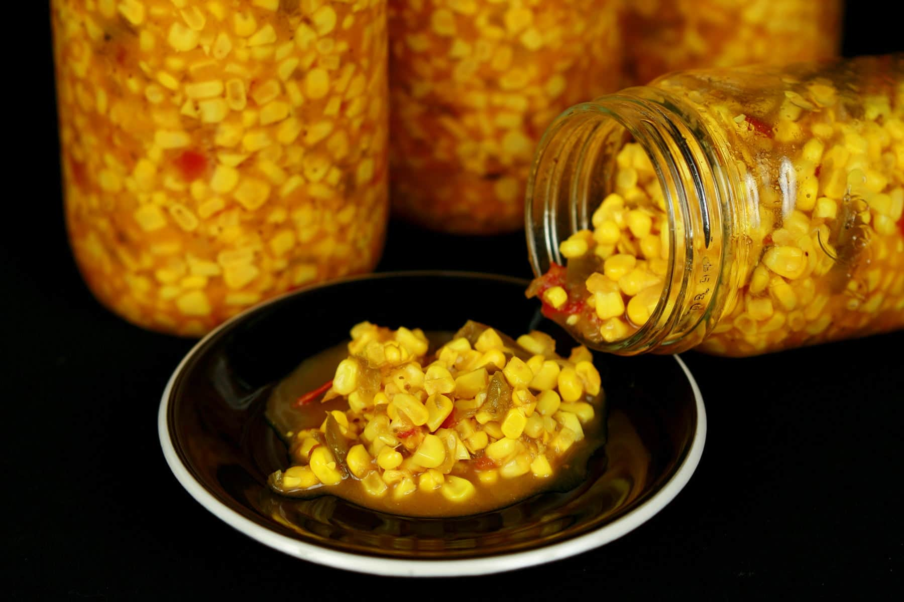 3 tall jars of sweet corn relish, behind a 4th jar being poured out onto a small black plate.