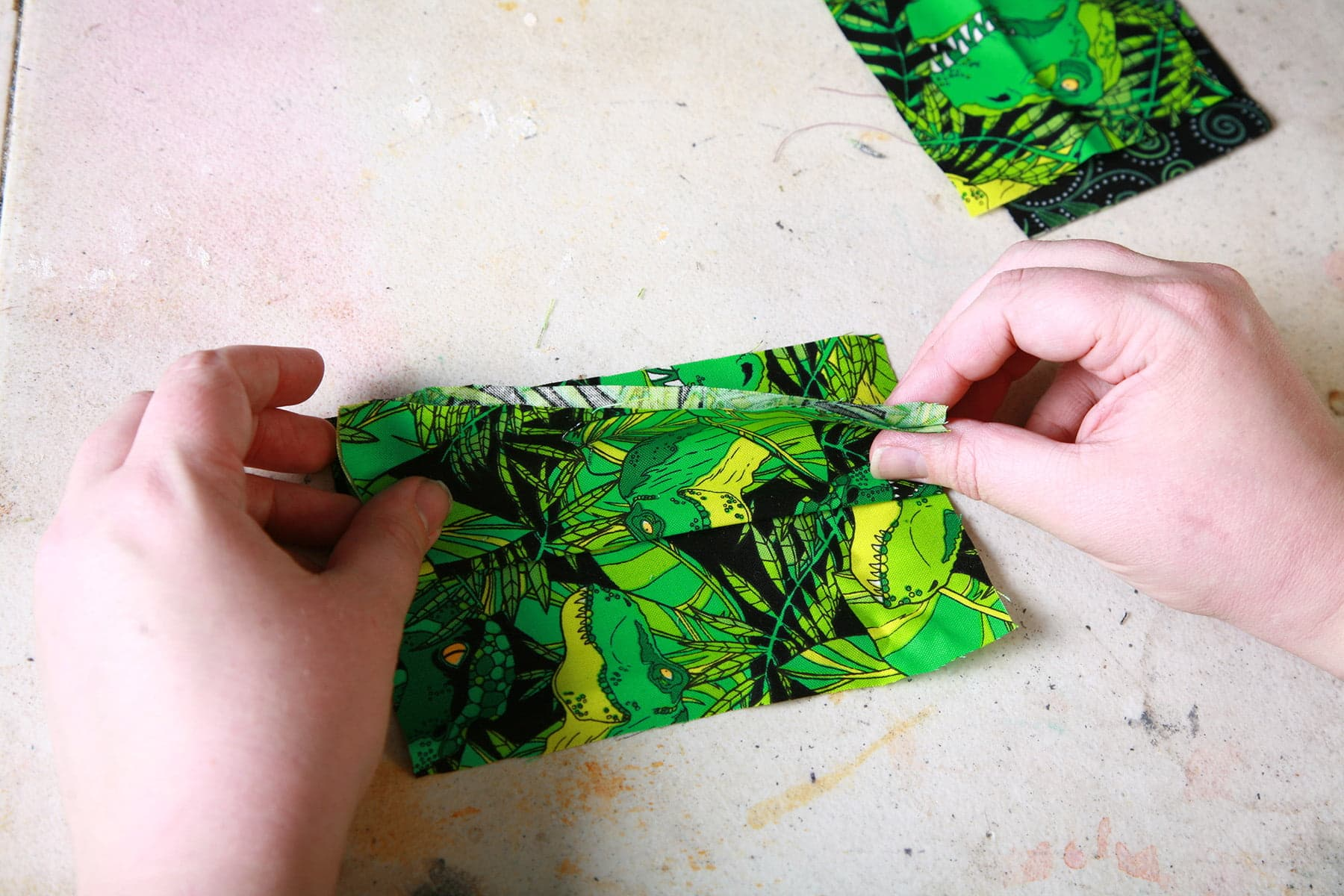 Two hands are shown folding a piece of fabric in half.