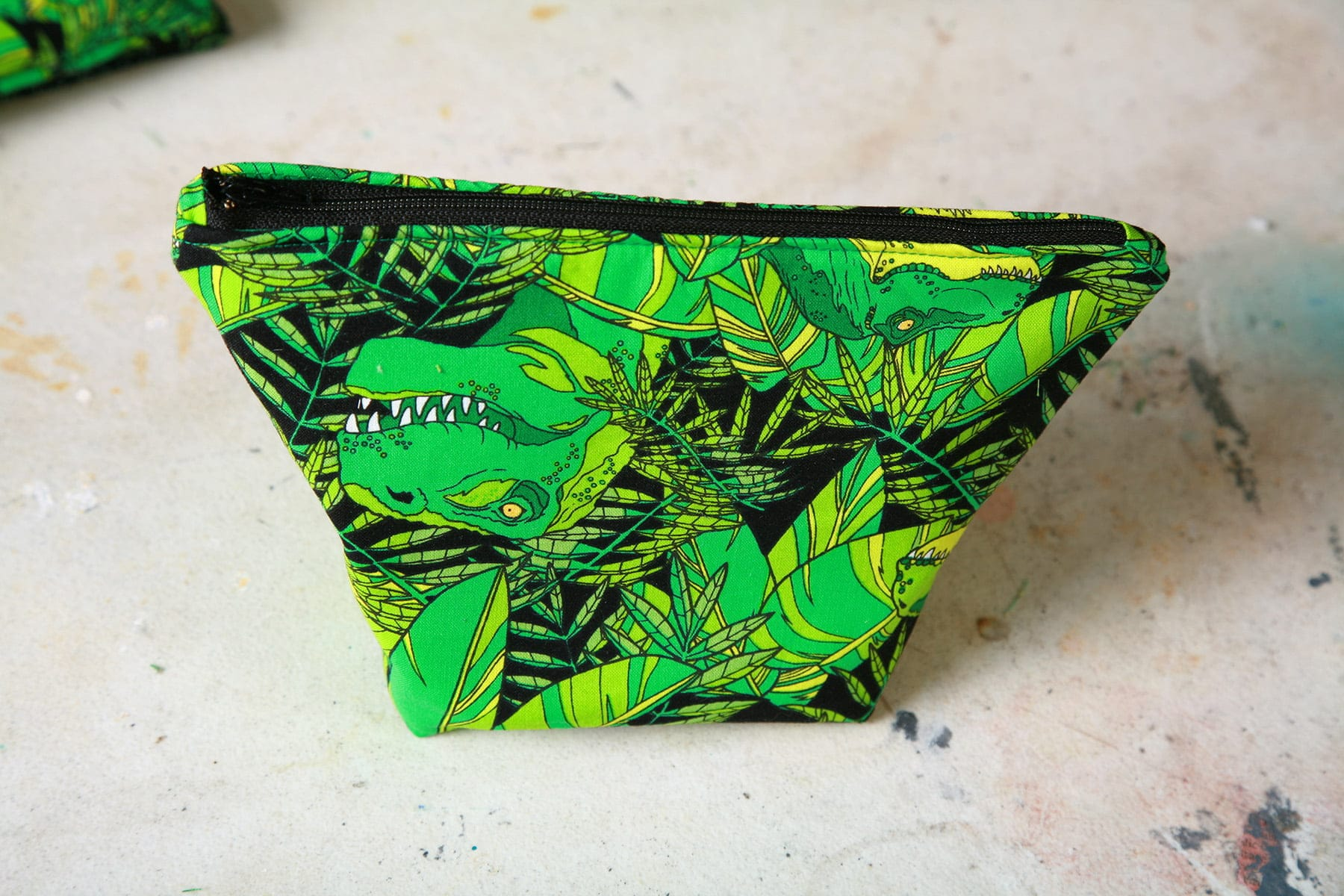 A finished makeup bag, made from a green dinosaur print fabric.