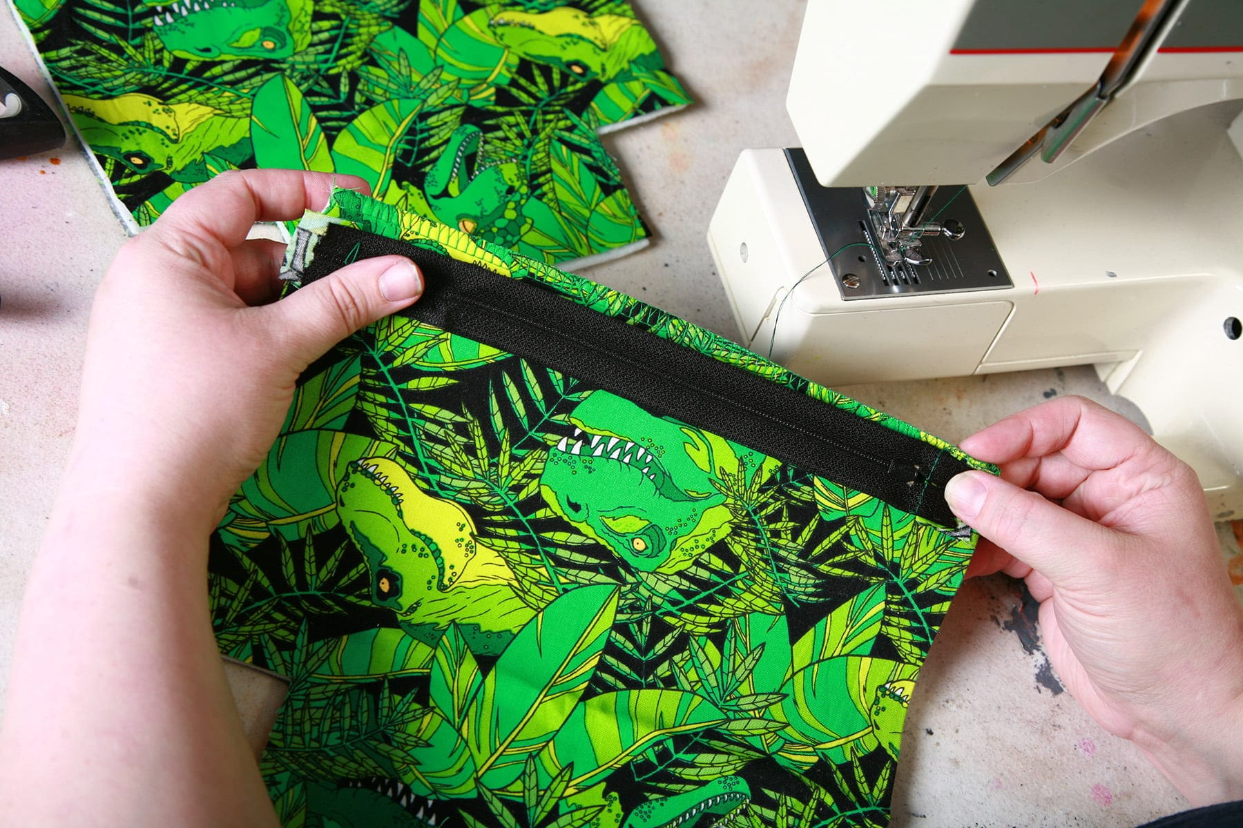 Two hands hold a black zipper against a piece of green dinosaur print fabric.