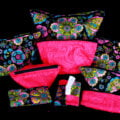 A large travel and makeup bag set - 6 bags of various sizes, two coin purses, and a tissue holder - are shown in front of a black background. The fabrics are a black print with colourful paisley design, and a mottled hot pink.