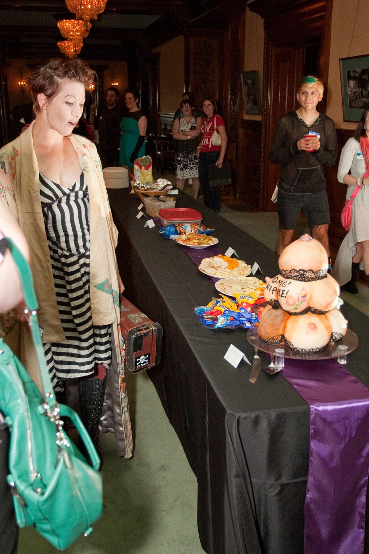 Amanda Palmer looking at her boob cake.