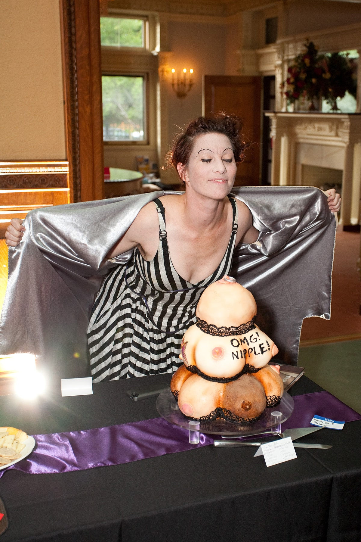 Amanda Palmer standing behind a cake that looks like a pile of breasts.