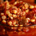 A close up view of roasted corn salsa for canning - corn salsa with tomatoes and peppers - in a glass bowl.