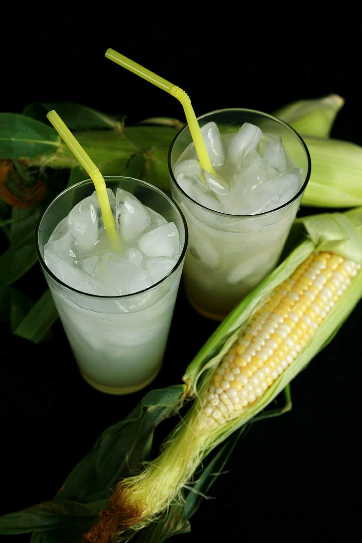 Two tall glasses of Quick Sweet Corn Soda.  The soda is pale yellow, with ice cubes and yellow straws.  There are two ears of corn next to the glasses.