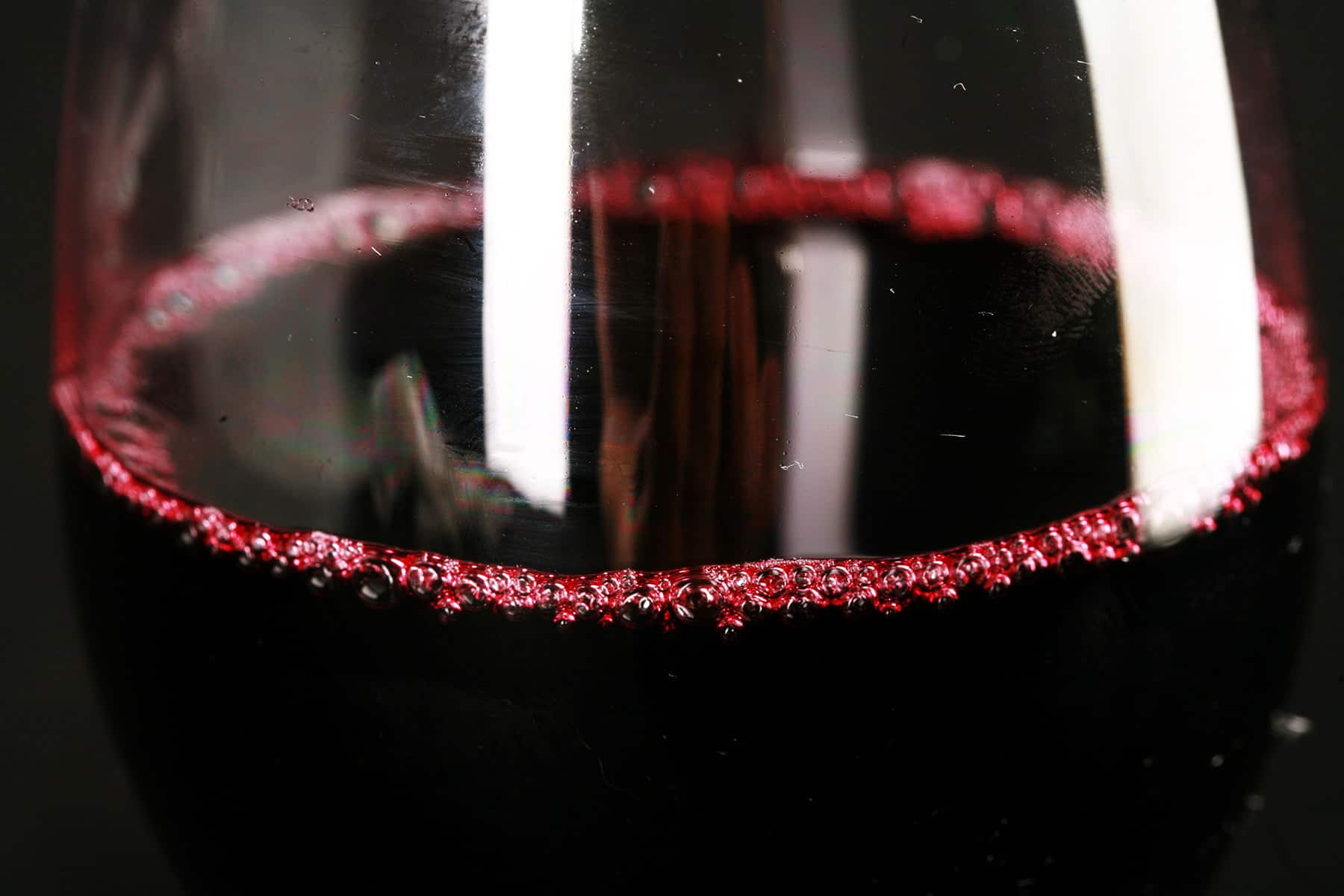 An extreme close up photo of a glass of blueberry wine.