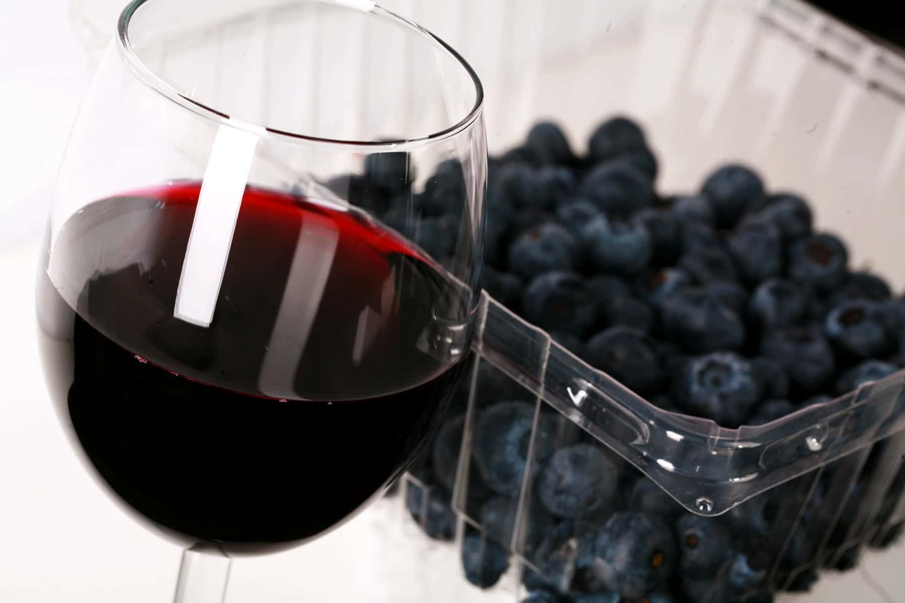 A glass of deep purple wine in front of a pint of fresh blueberries.