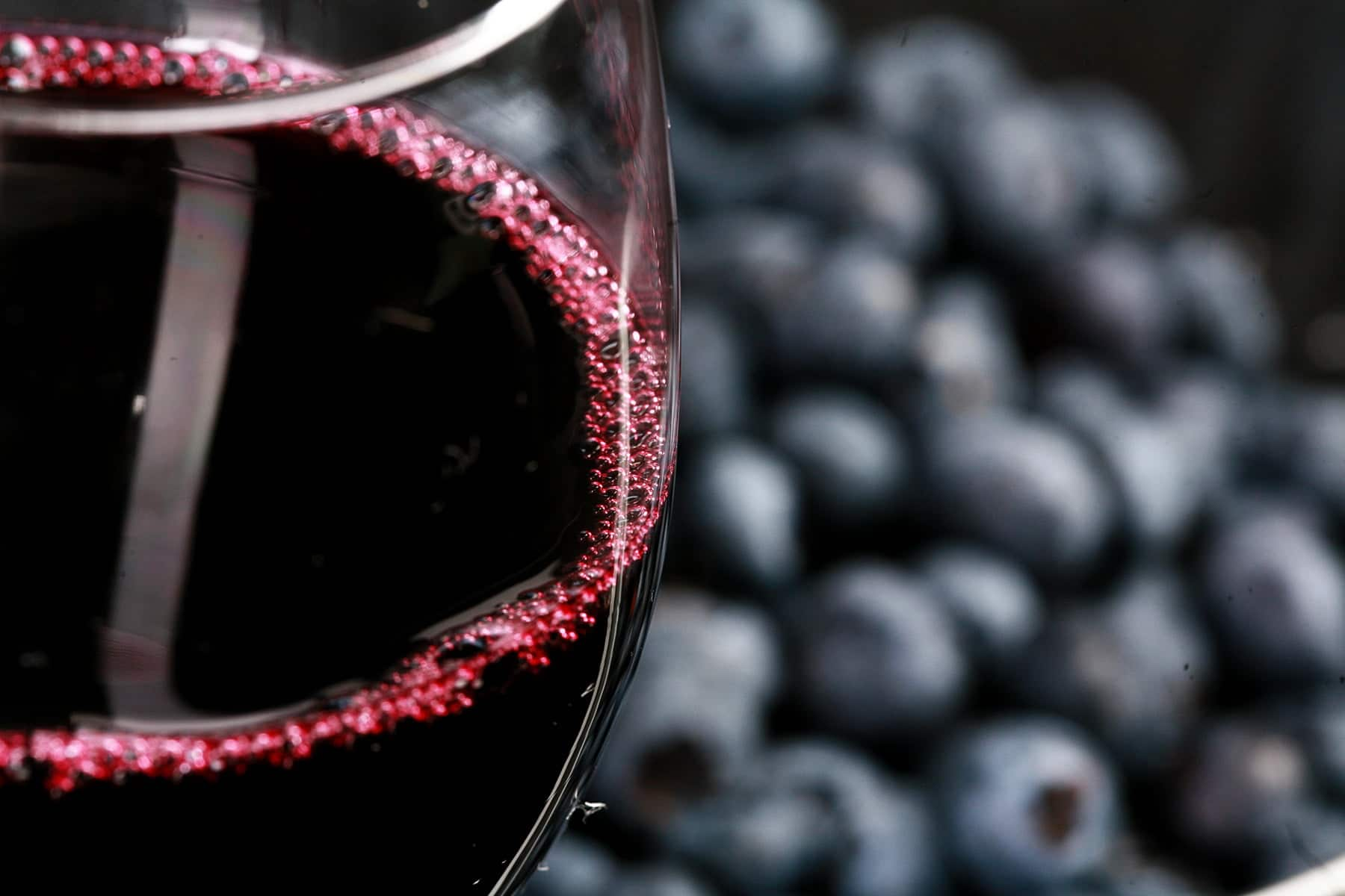 A glass of blueberry wine in front of a pint of fresh blueberries.
