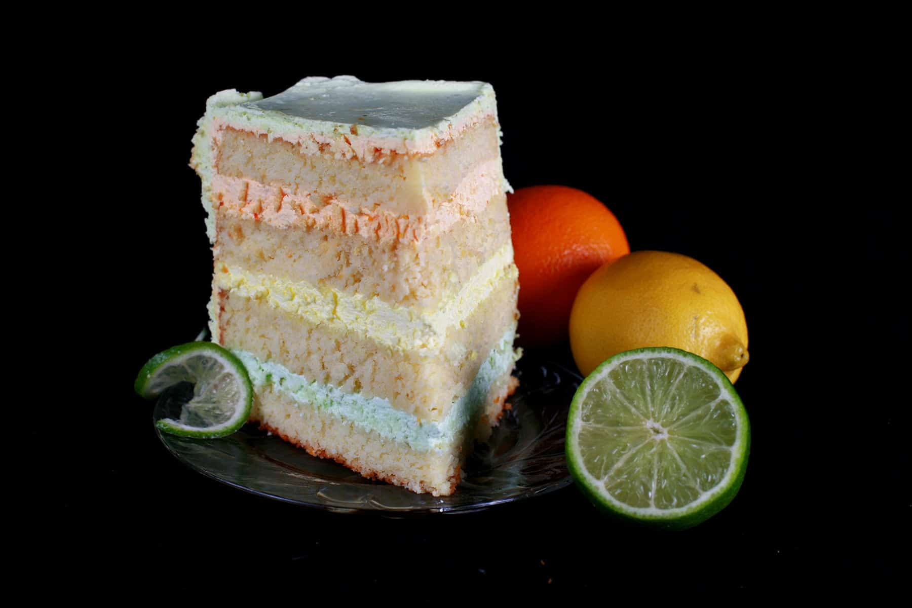 A slice of citrus splendor cake is shown on a plate, with an orange, lemon, and half a lime sitting next to it.
