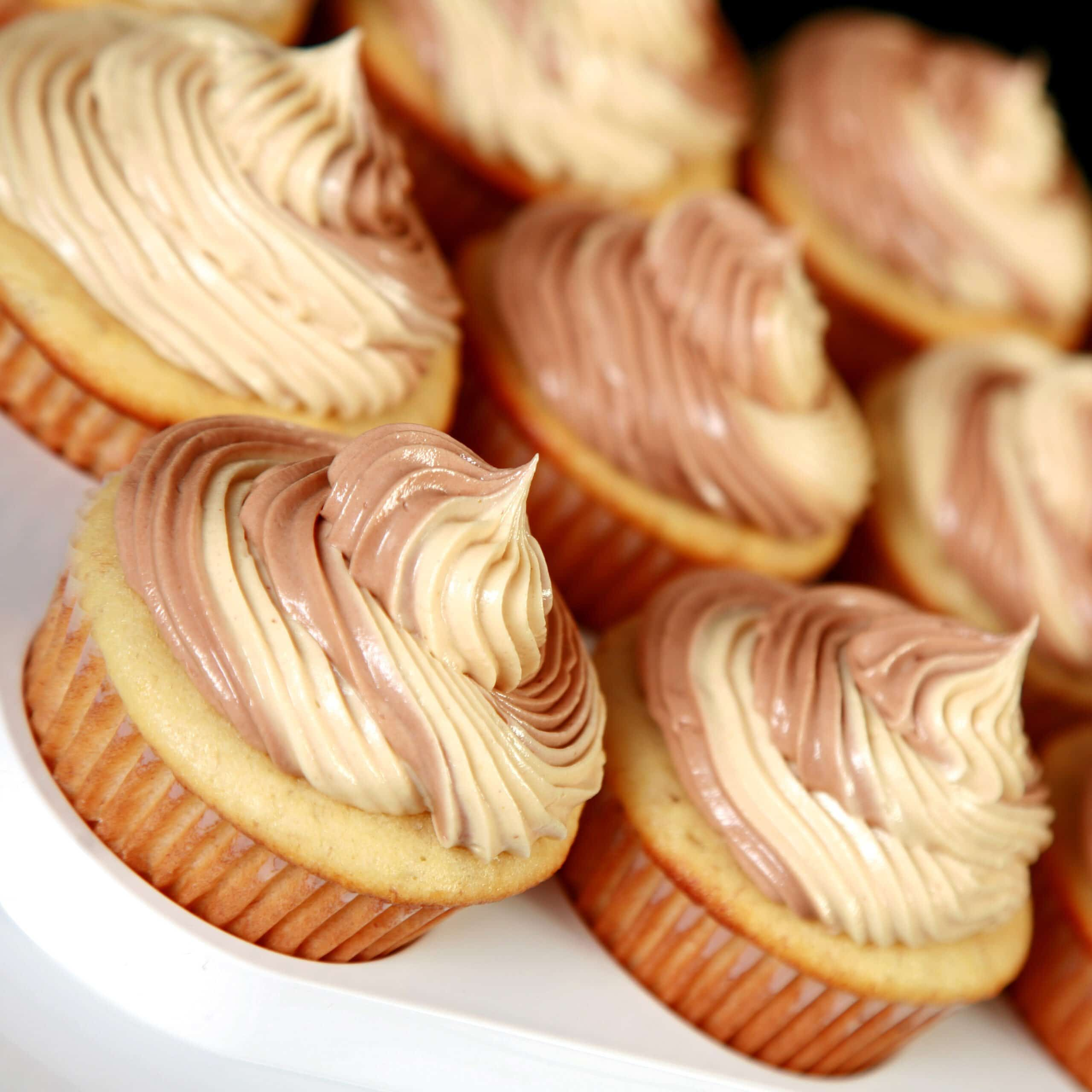 A tray of Fat Elvis Cupcakes - Banana cupcakes frosted with a two-tone swirl of Swiss Meringue buttercream, in both peanut butter and chocolate flavours.