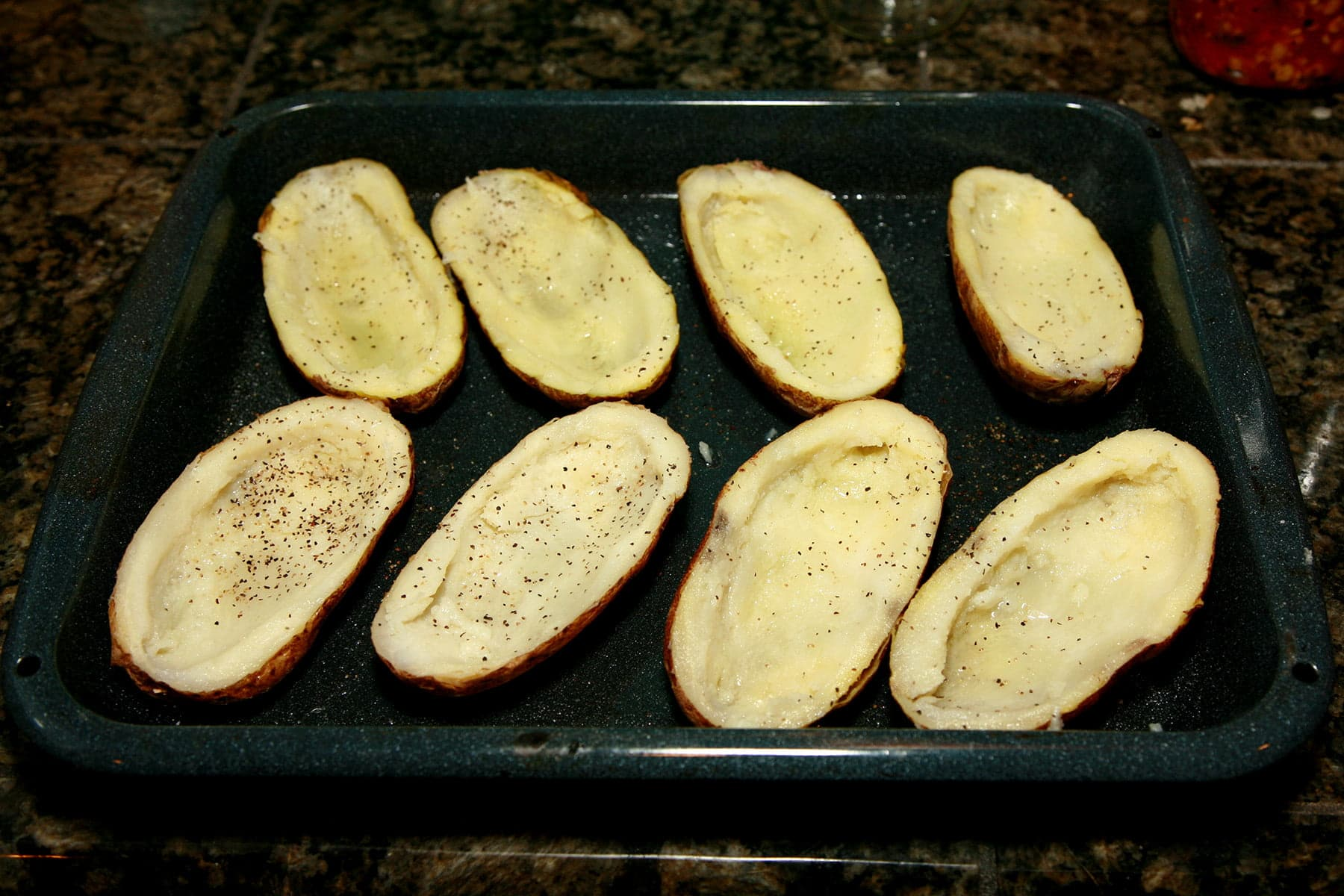 Hollowed out potato skins are arranged on a roasting pan.