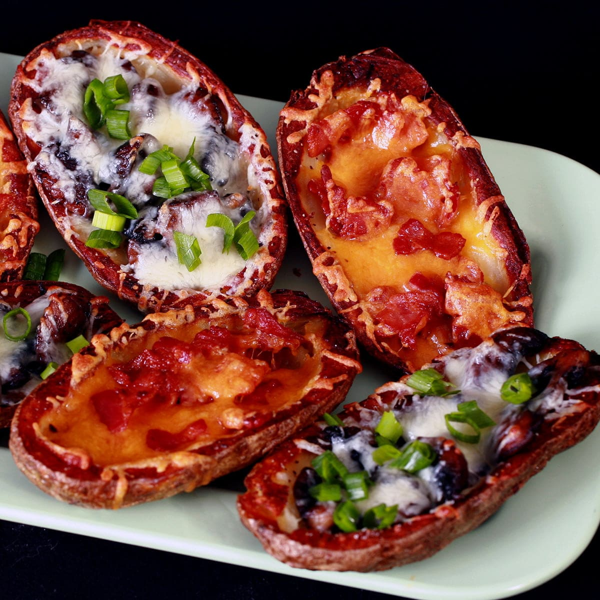 A pale green plate displays 8 baked potato skins. Half are filled with mushrooms and swiss cheese, the other half have bacon and cheddar as the filling, some topped with sour cream. Most potato skins are sprinkled with sliced green onion.