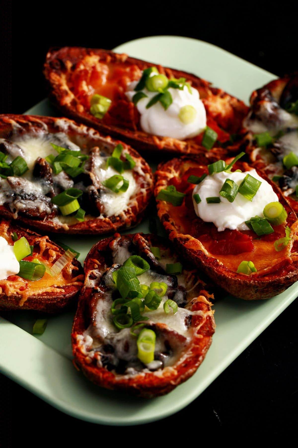 A pale green plate displays 8 bacon roasted potato skins. Half are filled with mushrooms and swiss cheese, the other half have bacon and cheddar as the filling, some topped with sour cream. Most potato skins are sprinkled with sliced green onion.