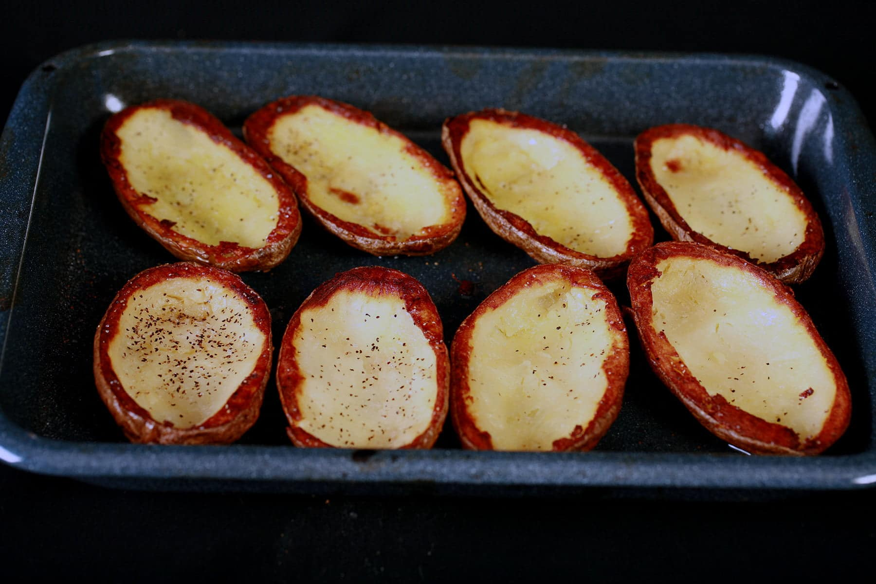 Hollowed out potato skins are arranged on a roasting pan. The upper edges are nicely browned.