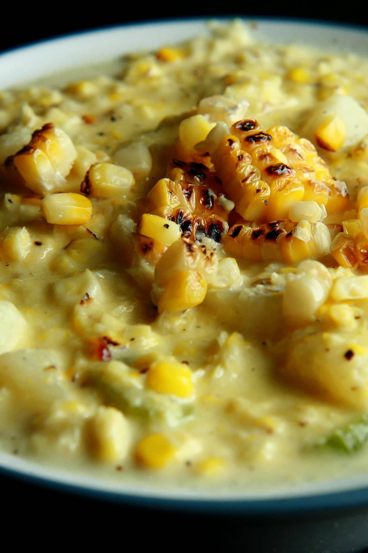 A white and cornflower blue bowl full of roasted corn chowder. Pieces of roasted corn garnish the surface of the soup.