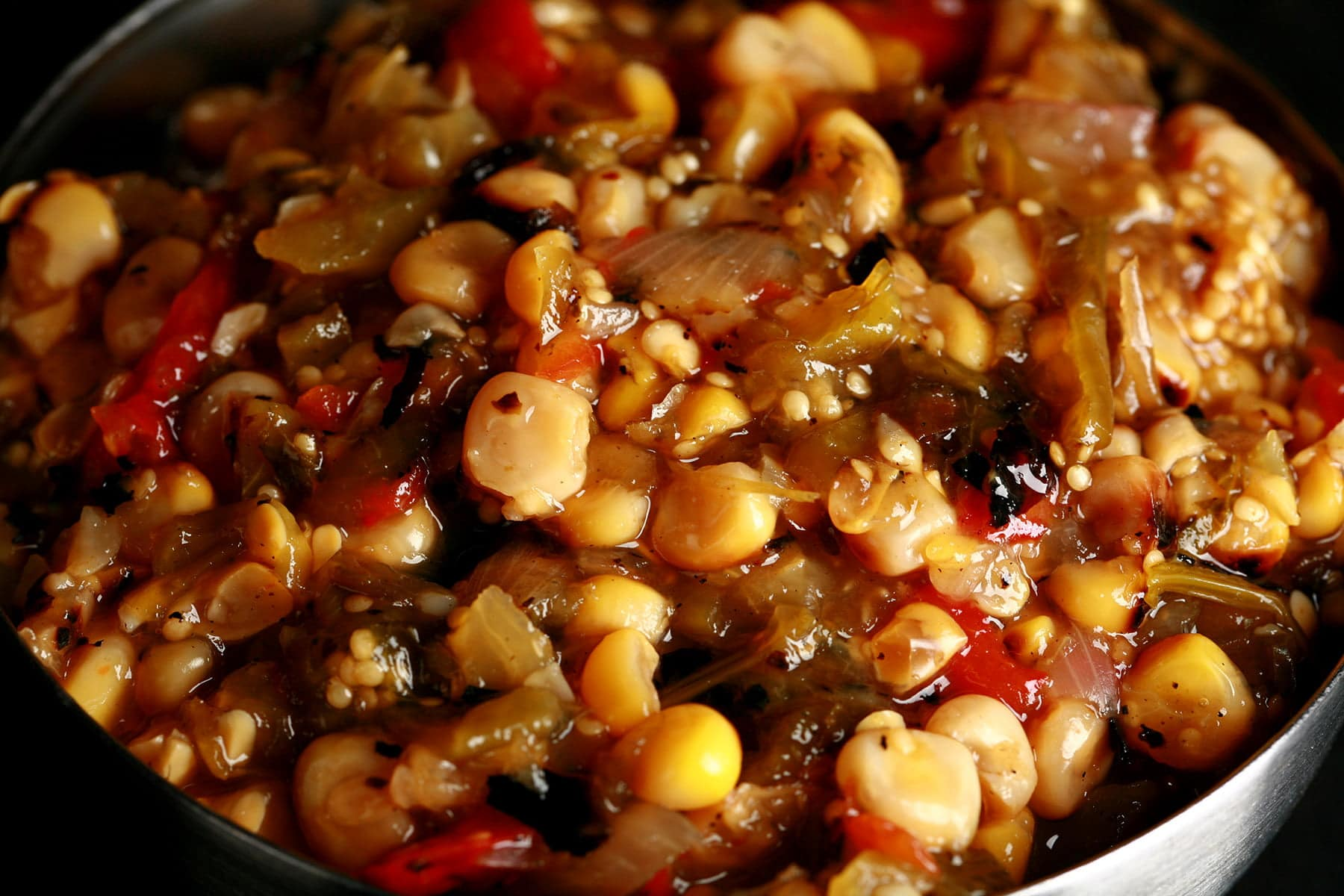 A close up view of a chunky roasted corn salsa verde - a green salsa with yellow corn and red peppers throughout.