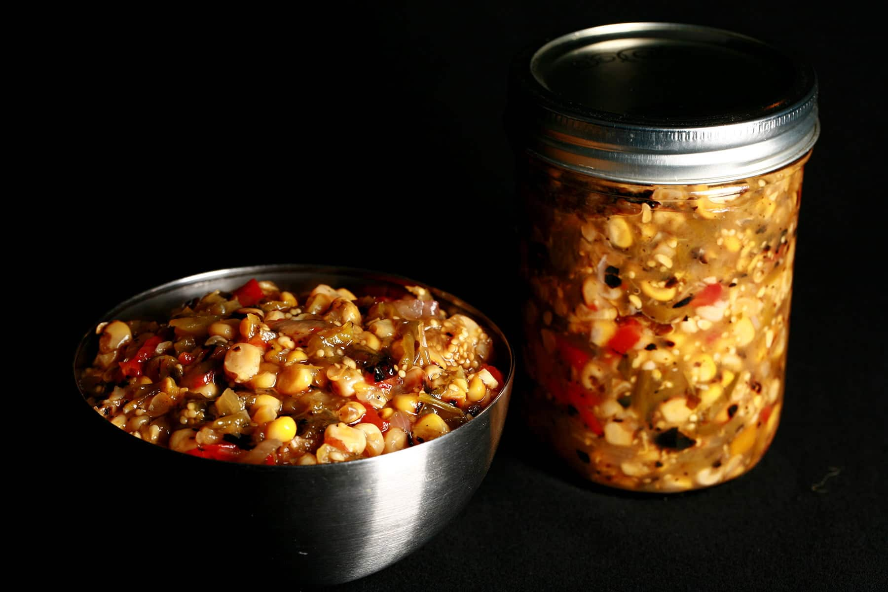 A bowl of a chunky roasted corn salsa verde - a green salsa with yellow corn and red peppers throughout. There is a jar of the same salsa behind the bowl.