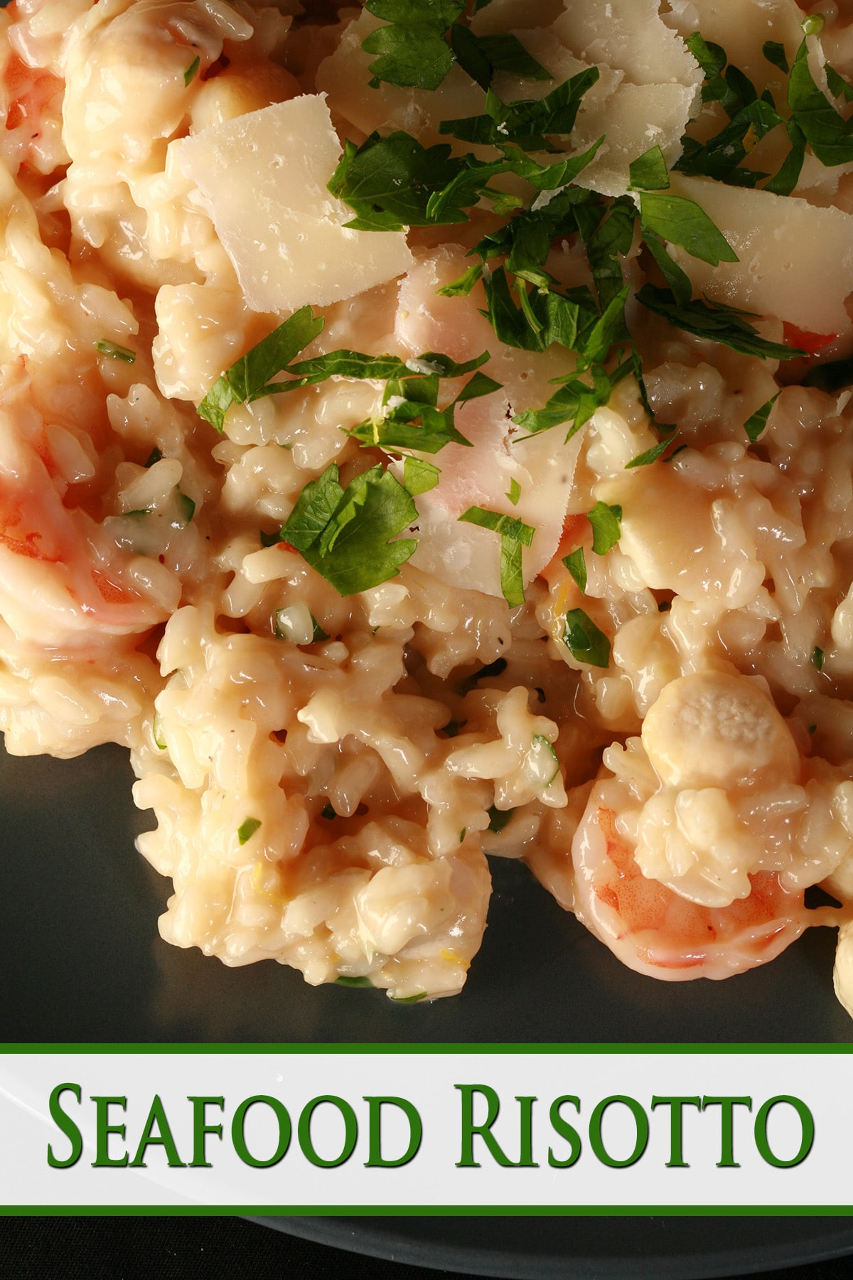 A close up view of seafood risotto on a plate. The top is scattered with chopped parsley and big flakes of Parmesan cheese.