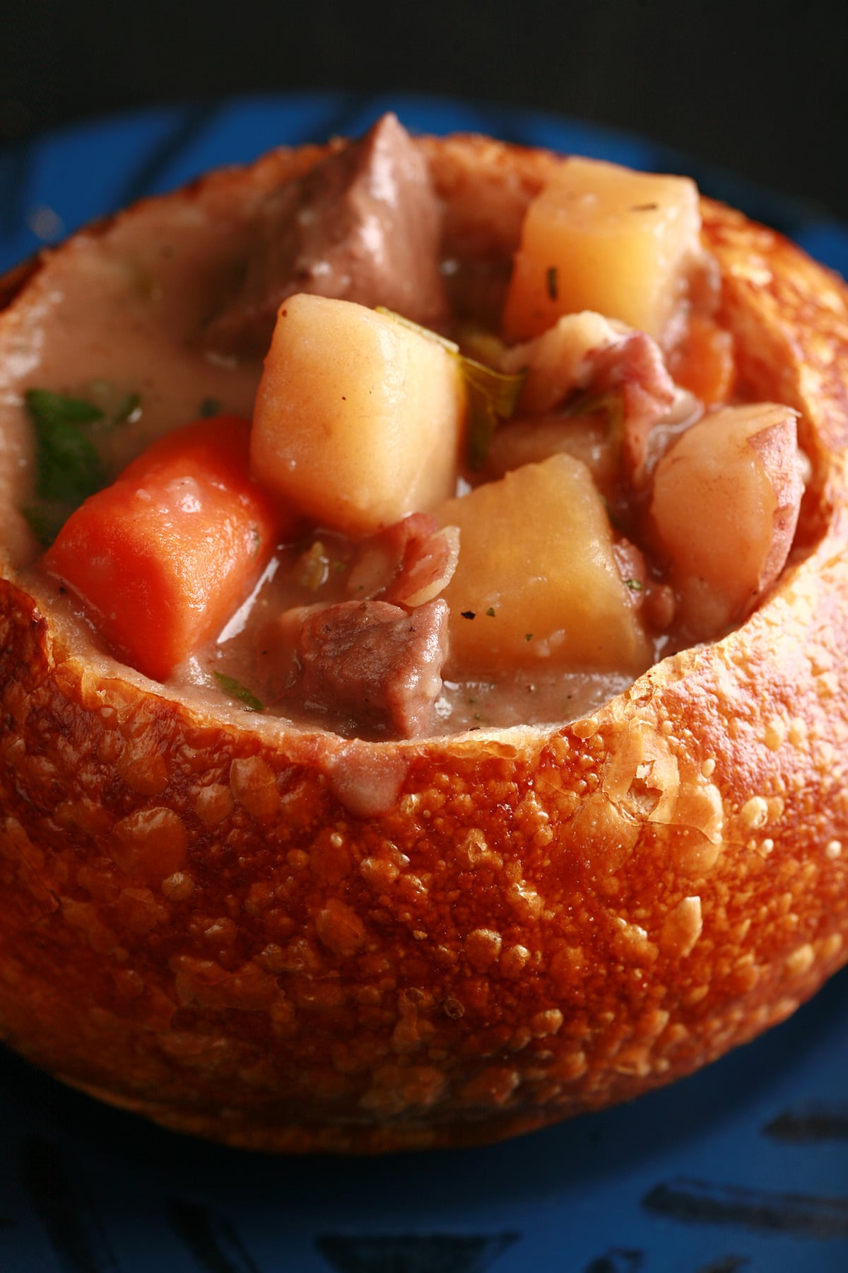 A bread bowl full of hearty beef stew. Chunks of beef, carrots, and potatoes are prominent.