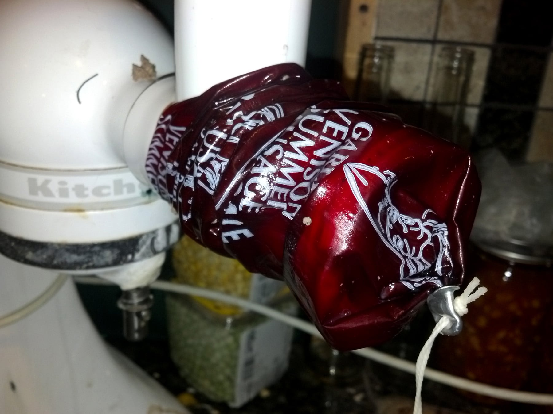 A red sausage casing being fed onto a kitchenaid stand mixer.