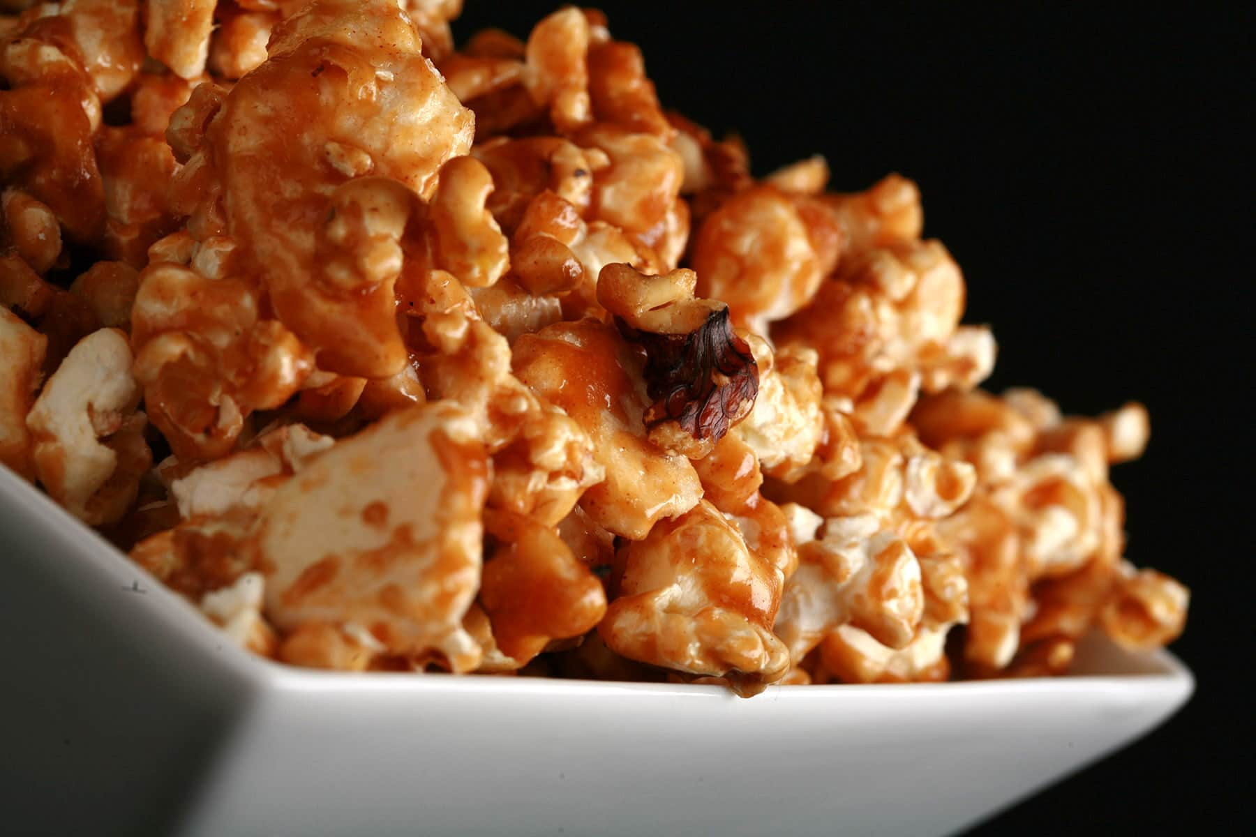 A close up view of a bowl of caramel popcorn with dried apples and cinnamon.
