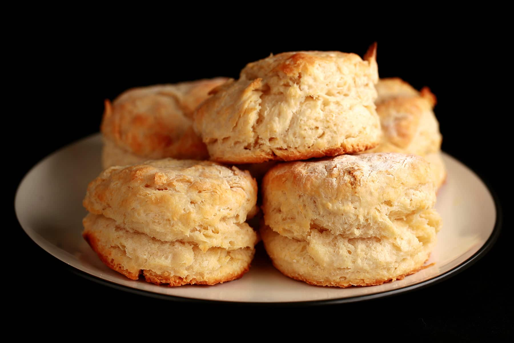 A small plate, stacked with golde, freshly baked biscuits.